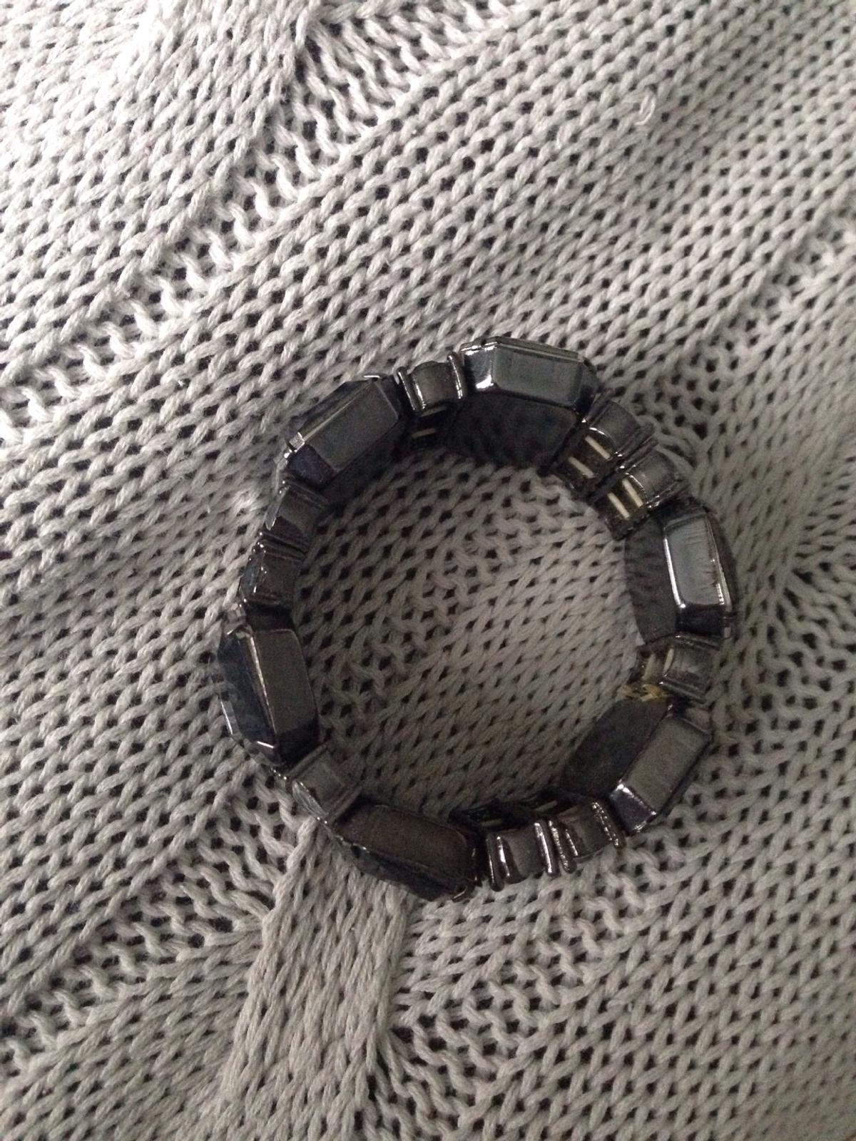 Large stones are smoky grey/black Smaller stones are smoky grey and clear This is an elasticated stone bangle