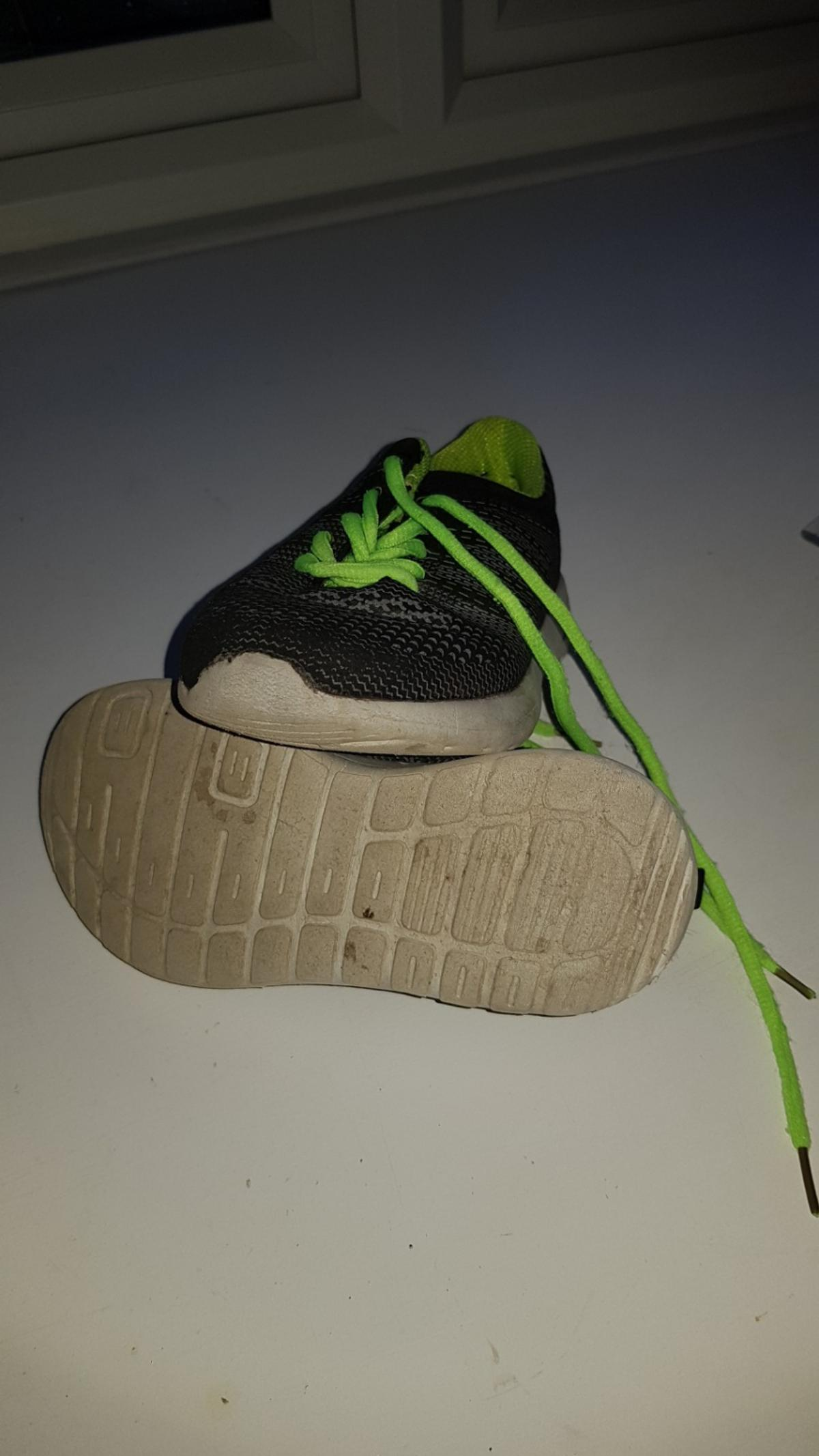 Nutmeg trainers size 11 boy/ girl in vg used condition dark grey/black with bright green laces