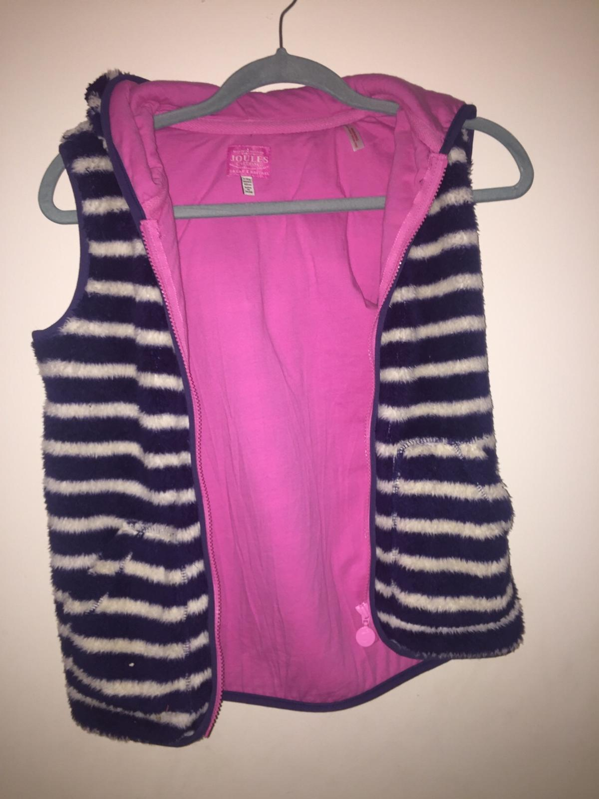 It's fluffy on outside and has pink material on inside. It has a hood and zips up. Size 11-12 years old.