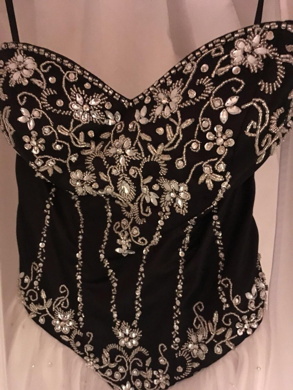 Only been worn once and in excellent condition.  It's an American size 4 (UK size 8-10) Black satin bodice with jewelled and sequinned detail. Laced up corset back (to allow adjustment) with a white tulle net over a satin skirt with sequins and jewels.  Bought it for £425 so looking for £250 (O.N.O)