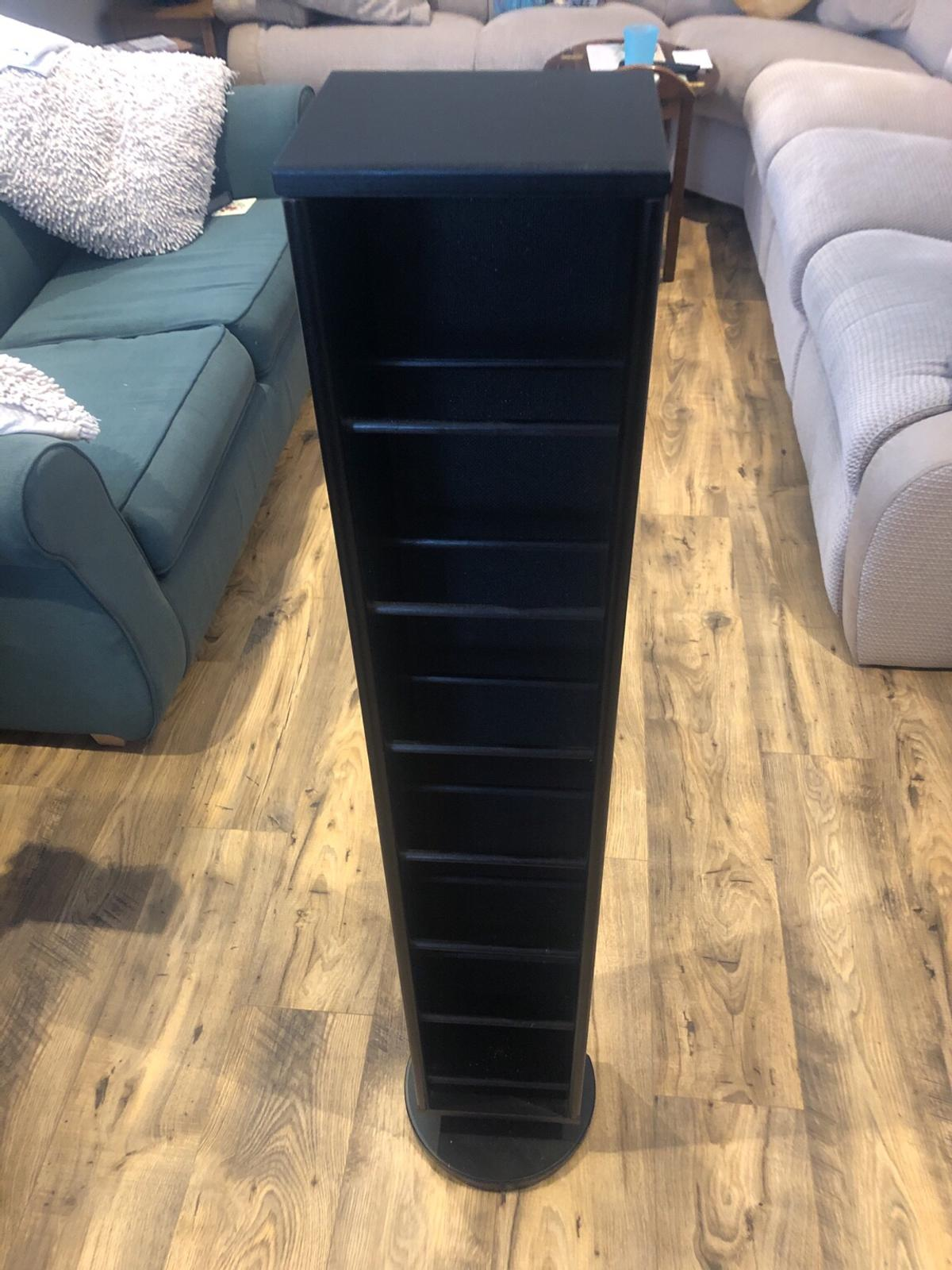 Black, wooden CD tower stand on rotating base.