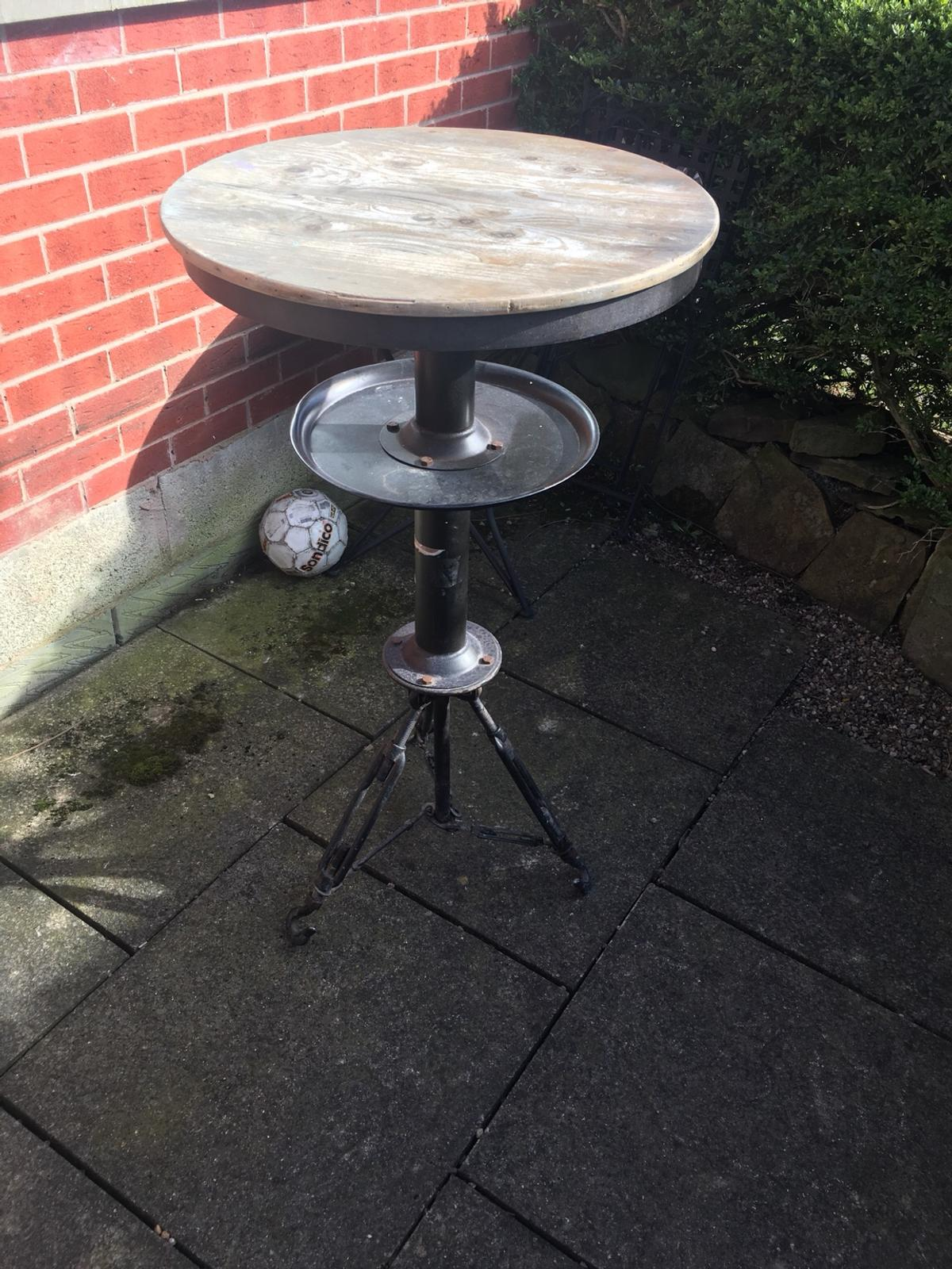 A beautiful wooden top with metal stand. A great rustic bar table. Round too
