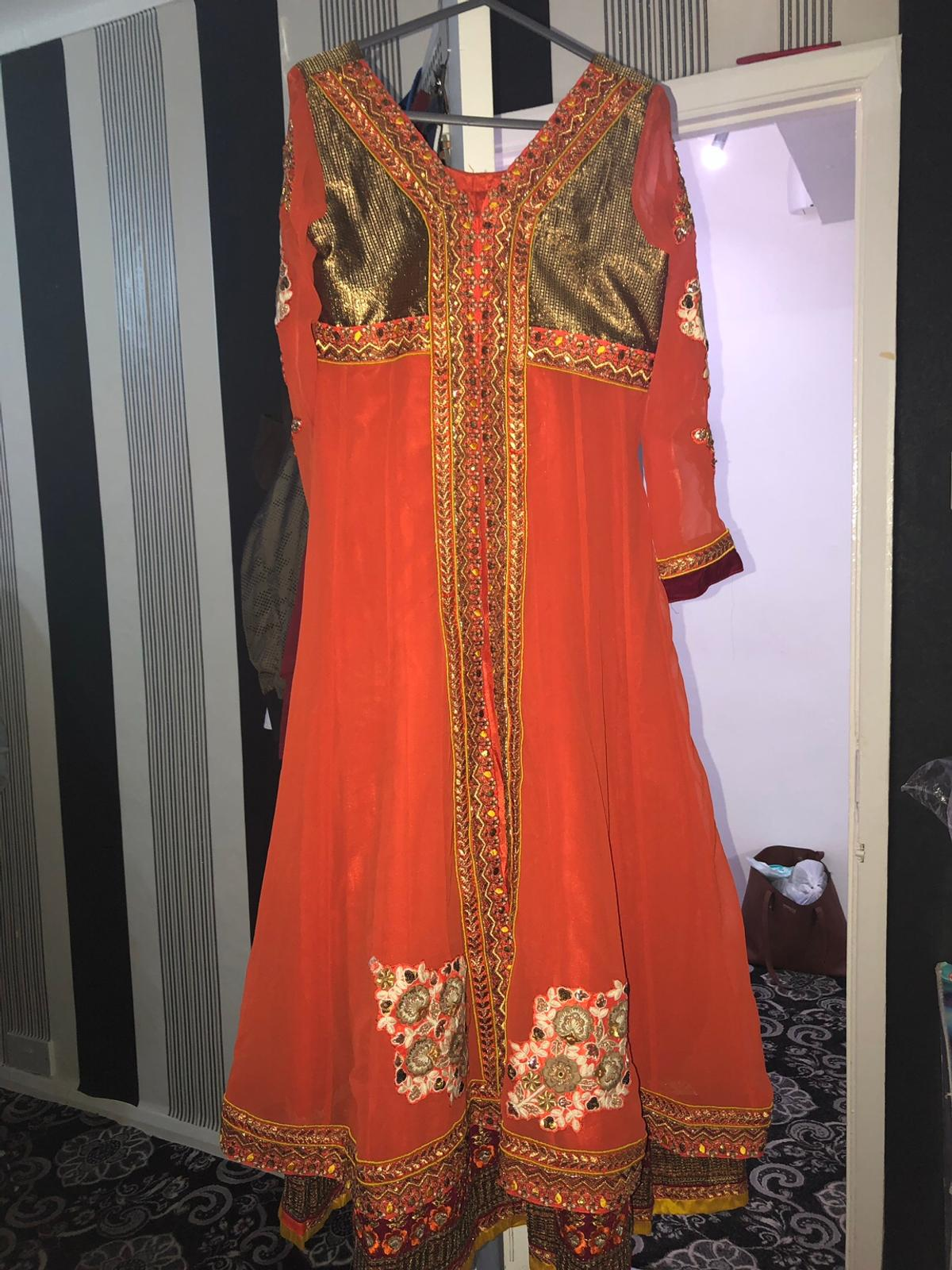 Orange with beautiful embroidery work Comes with churridar and dupatta Brand new Have put on weight so no chance of wearing it Size 10-12-14 Can be adjusted lots of margin