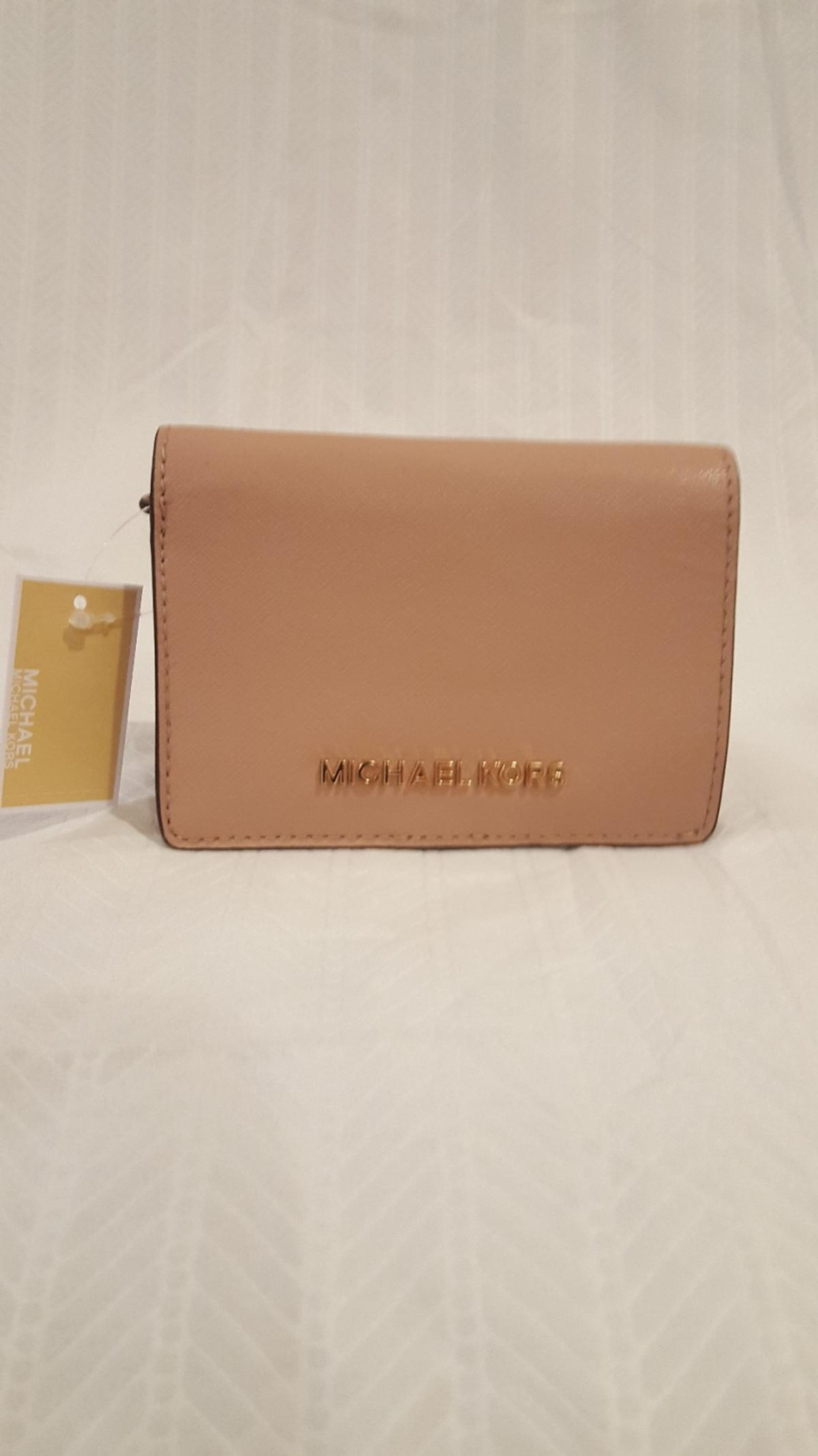 """Michael Kors Medium Jet Set Travel Slim Wallet *Brand New!! Beautiful fawn color, front flap snap closure. Logo on front. 6 card slot, currency slot, zip pocket, and ID window. Measures 3.5""""H x 1.5"""" D"""