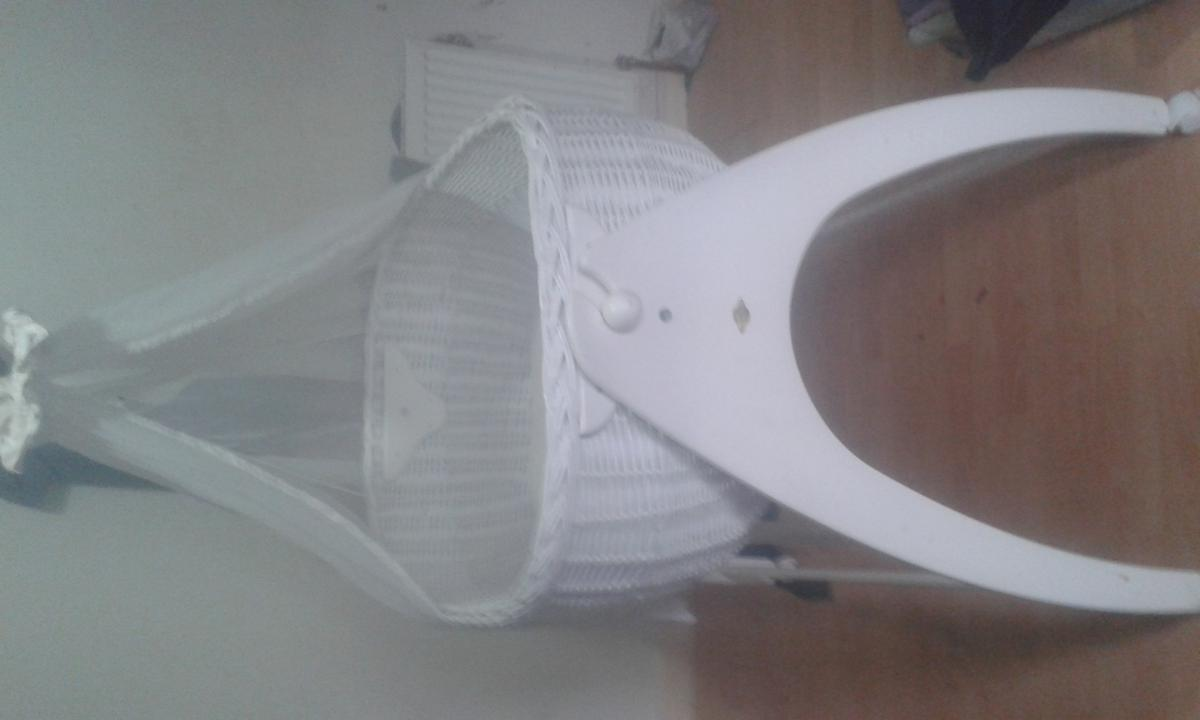 White wicker bassinet with mattress and white voile it has lock in wheels for safety