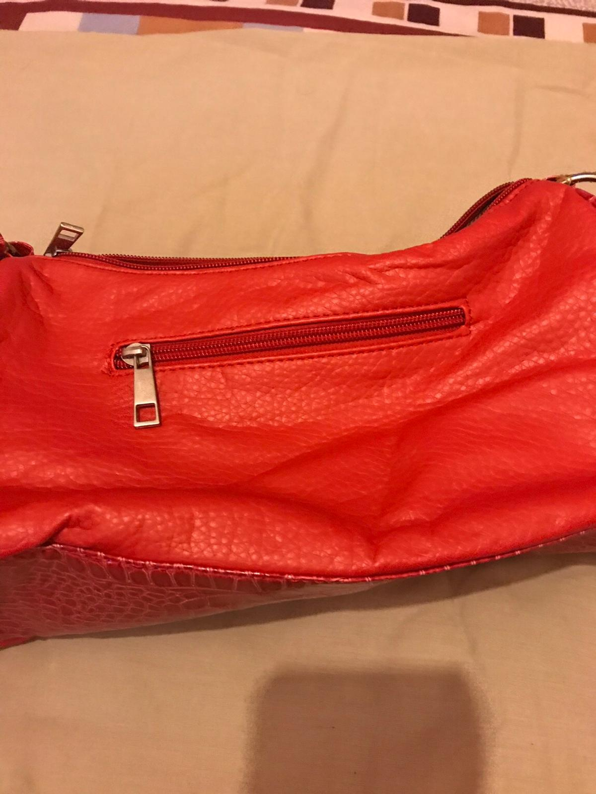 Soft leather studded red stylish shoulder bag has a 2 small pockets on the side and beautiful bow style bag brand new in excellent condition