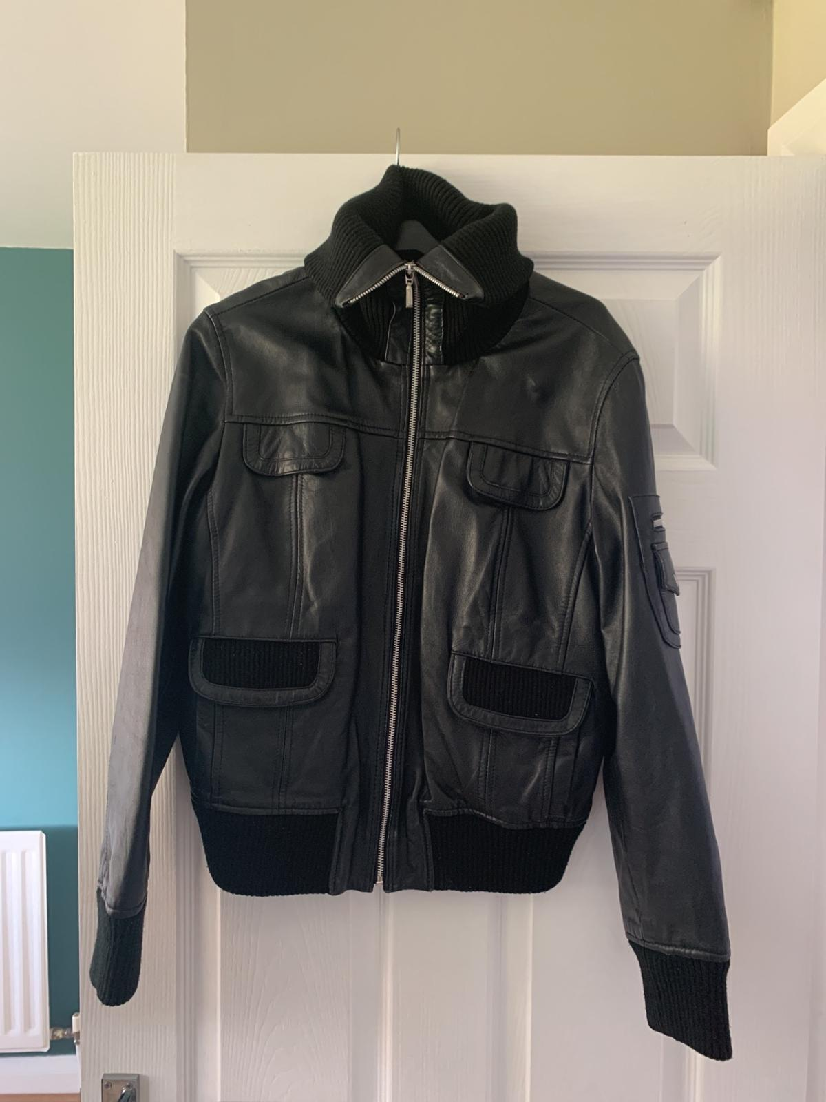Black leather jacket has a small rib on inside where tag has been