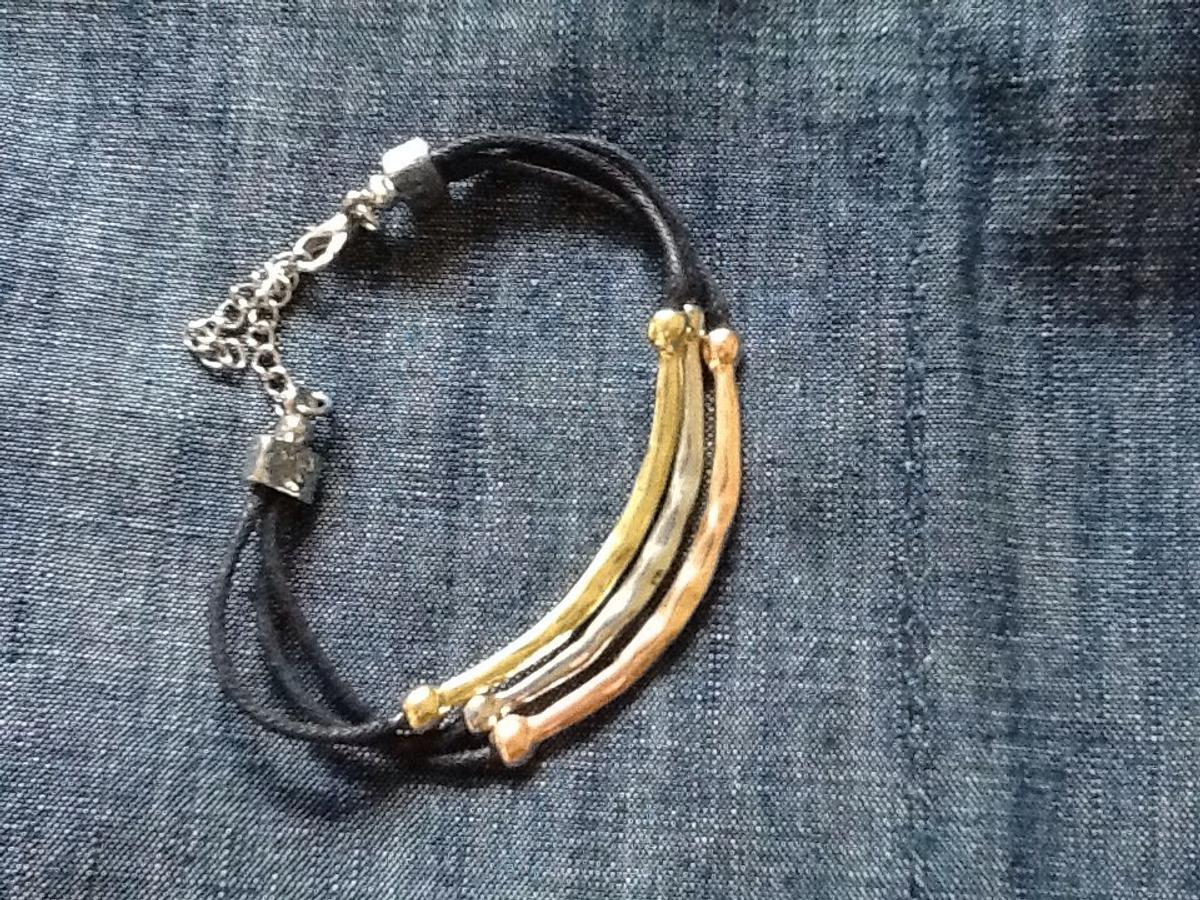 3 stringed bracelet with a different coloured metal on each string . Gold ,bronze and silver. Fashions with a clasp.