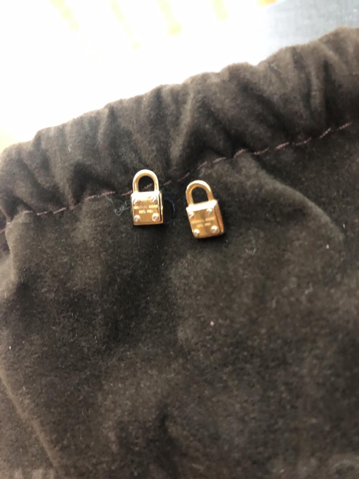 Tiny locks with silver screws and branding. No backs included.