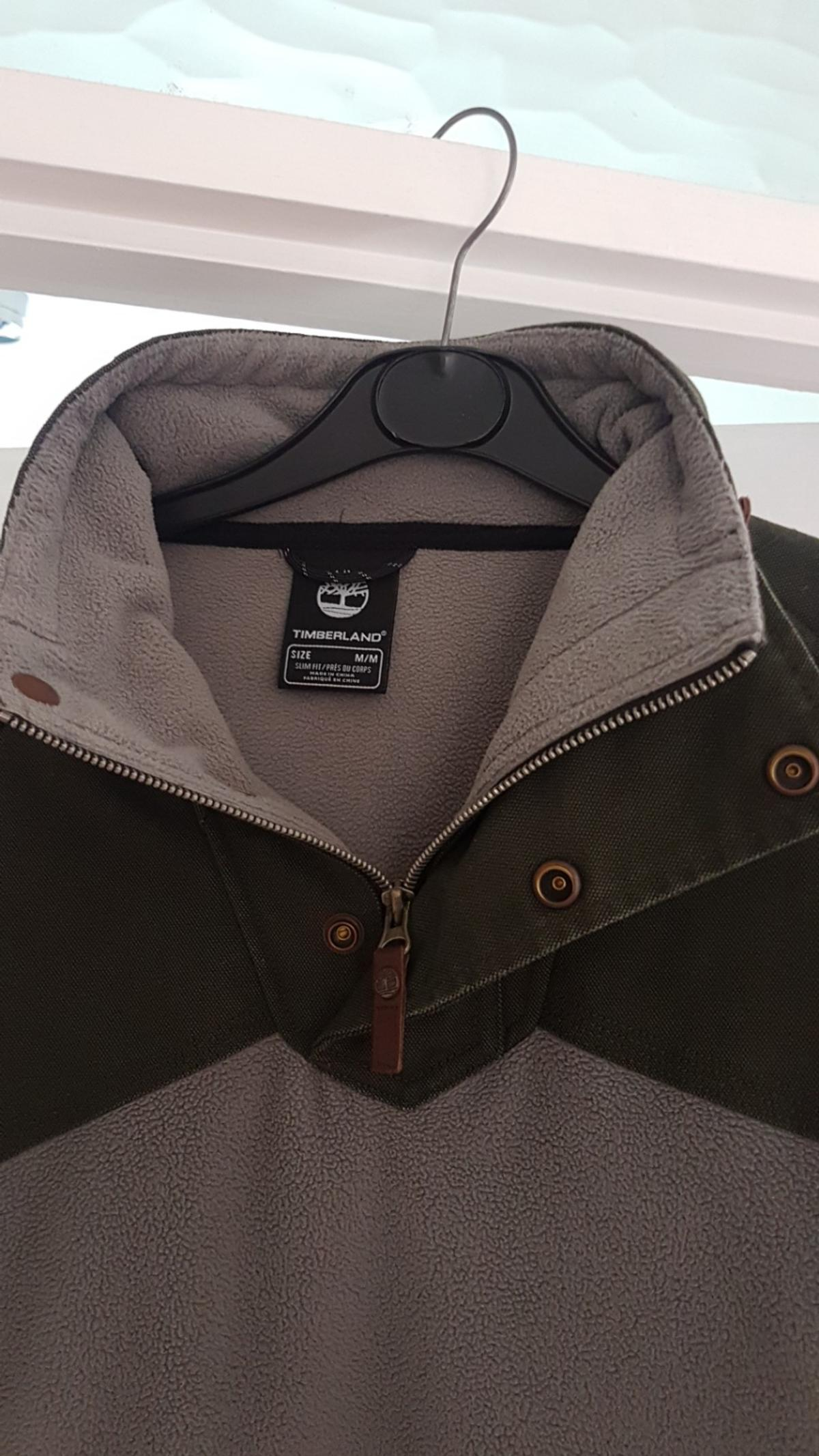 Timberland khaki top m.leather detailing to collar and back neck line.bit of thraying to hem.cuffs with holes in.used con.