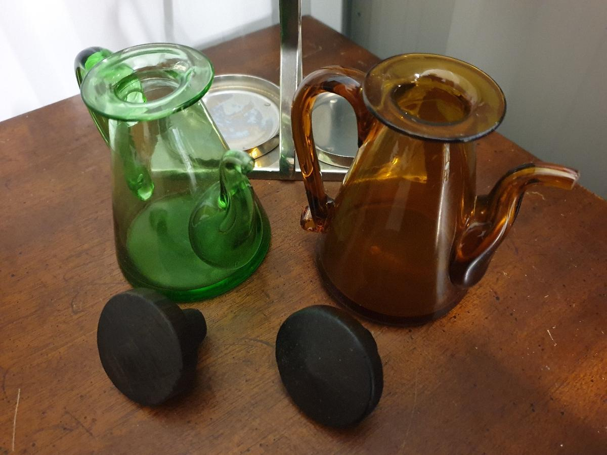 *VINTAGE RETRO FRENCH DRESSING OIL SALAD CONDIMENT SET *COMPLETE WITH GREEN & BROWN GLASS JARS & STAINESS STEEL STAND *LOVELY KITCHEN TABLEWARE DECOR *DIMENSIONS: OVERALL HEIGHT 15cm OVERALL LENGTH 15cm OVERALL WIDTH 7.5cm JAR HEIGHT incl stopper 10cm *IN VINTAGE CONDITION WITH LESS THAN EXPECTED WEAR FOR AGE AND USE, APPEARS TO HAVE BEEN RARELY OR NEVER USED, PLEASE SEE PHOTOGRAPHS *ALL ITEMS ARE CAREFULLY PACKED TO PROTECT DURING DELIVERY *COLLECTION BY ARRANGEMENT DUDLEY DY2 JH4606