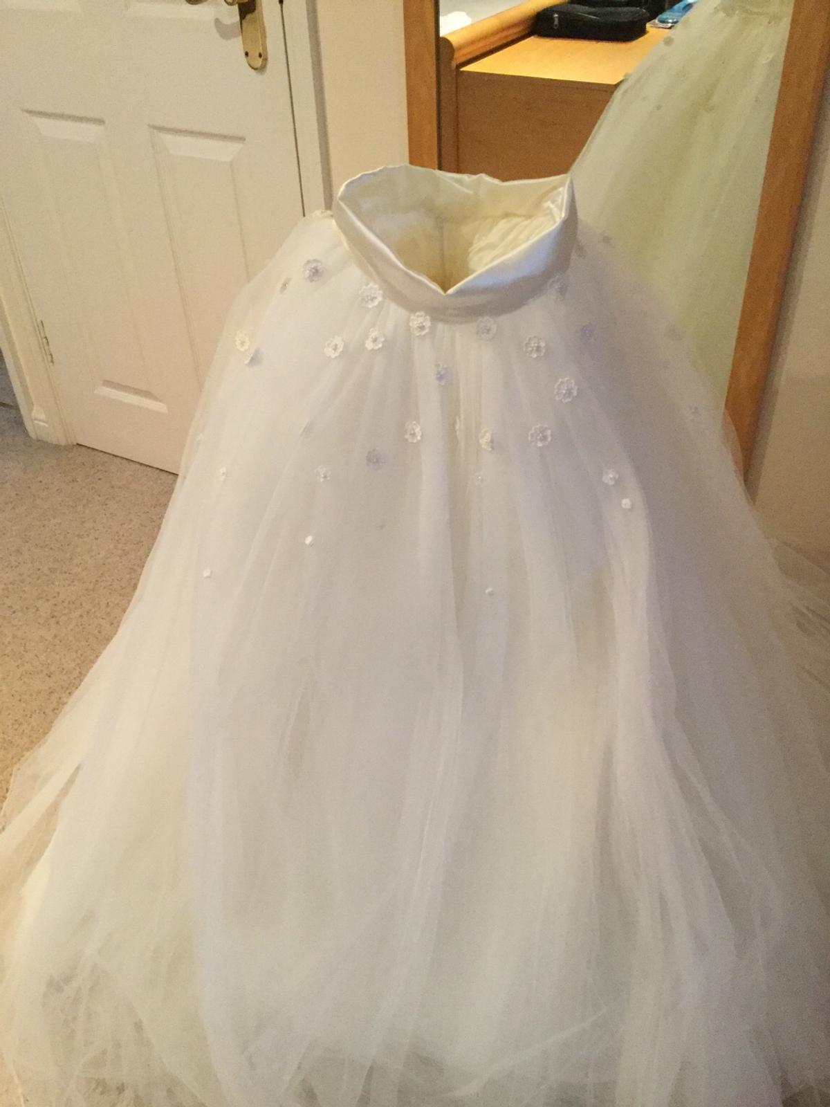 A bespoke designed full tulle net wedding skirt ,detachable train and matching veil. Made for a size 8 bride 5ft 6 inches tall in a moderate heel. Can be worn as a complete wedding day outfit with any blouse/ basque top. Hand embellished with cascading flowers over the skirt and veil. Stunningly feminine. Comes blessed from a very happy marriage of many years. Complete with cotton clothes protector and waterproof dust cover.