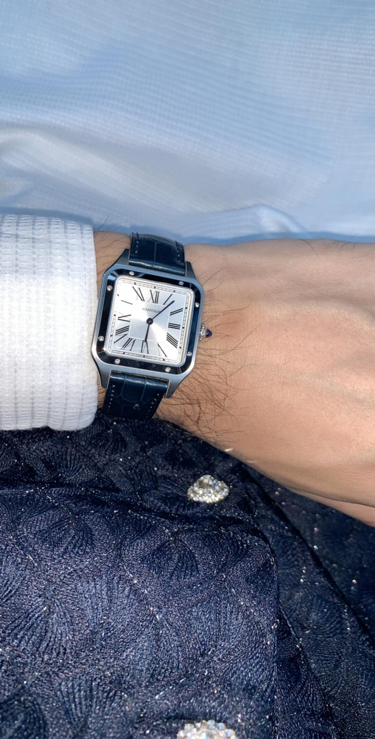 Bought 6 months ago. Only worn for 2 hours. Like brand new. Box and papers included. Cartier Warranty Card. Santos-Dumont watch, large model, quartz movement. Steel case, beaded crown set with a blue synthetic cabochon-shaped spinel, silvered satin-brushed dial with sunray effect, Roman numerals, blued-steel sword-shaped hands, sapphire crystal, navy blue alligator-skin strap, steel ardillon buckle. Case dimensions: 43.5 mm x 31.4 mm, thickness: 7.3 mm. Water-resistant to 3 bar approx. 30 metres