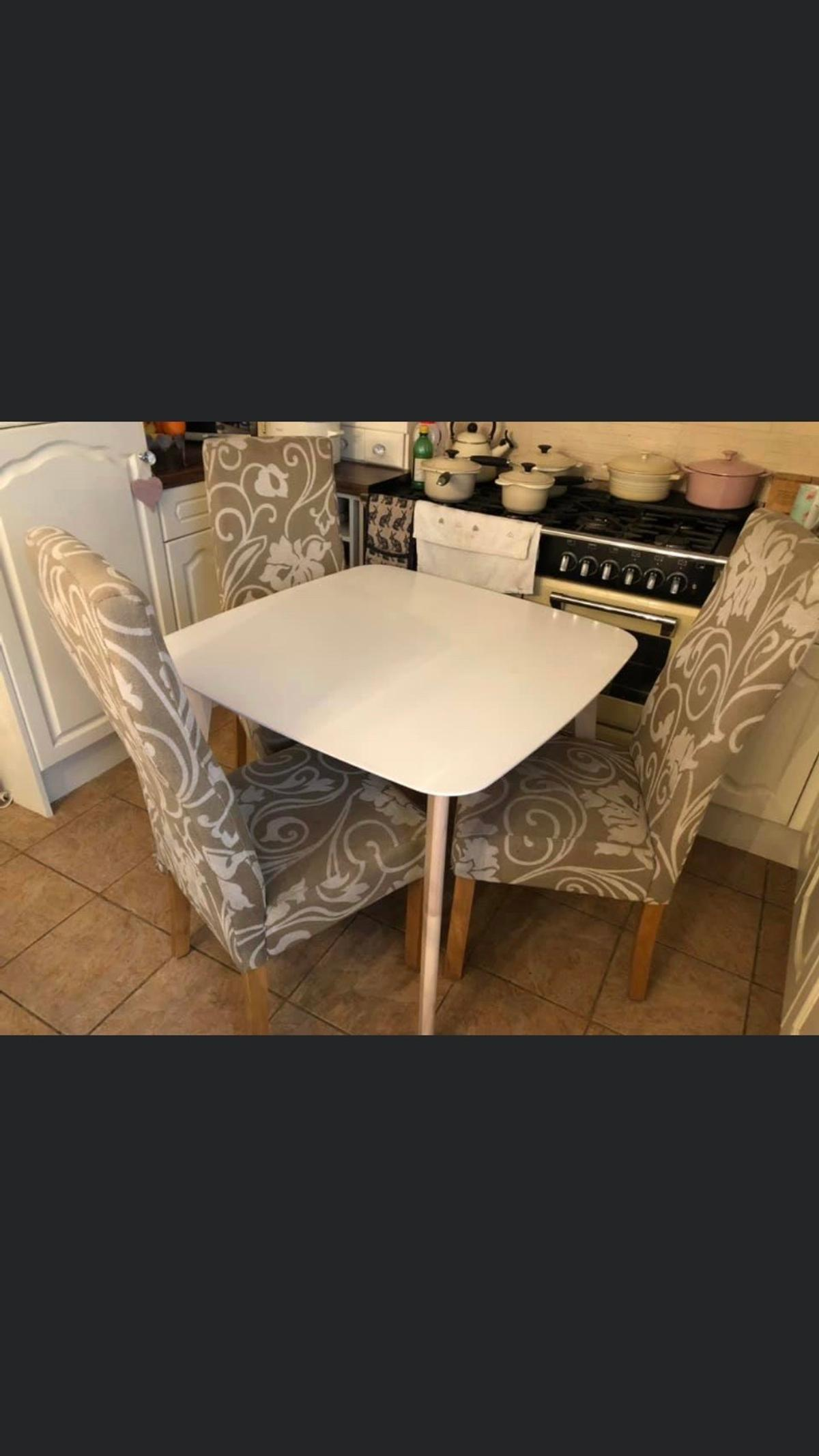 Lovely table by Julian Bowen in white with beech legs and three patterned chairs , measurements of the table are 90 cm by 90 cm, height 75 cm , perfect for kitchen or dining room