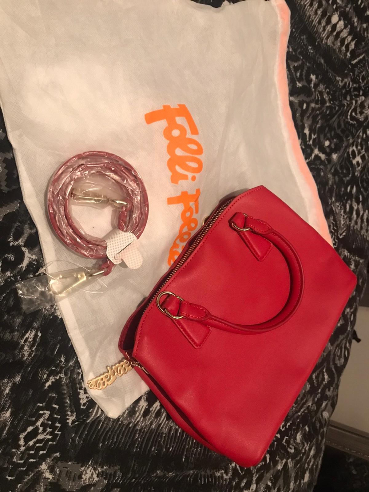 Here I have a brand new genuine folli follie bag from Selfridges with strap still in wrapping also comes with original bag. Never used.unwanted gift. HD2. Red. RRP £125. Length 25cm, Width 10cm, Height 17.5cm)