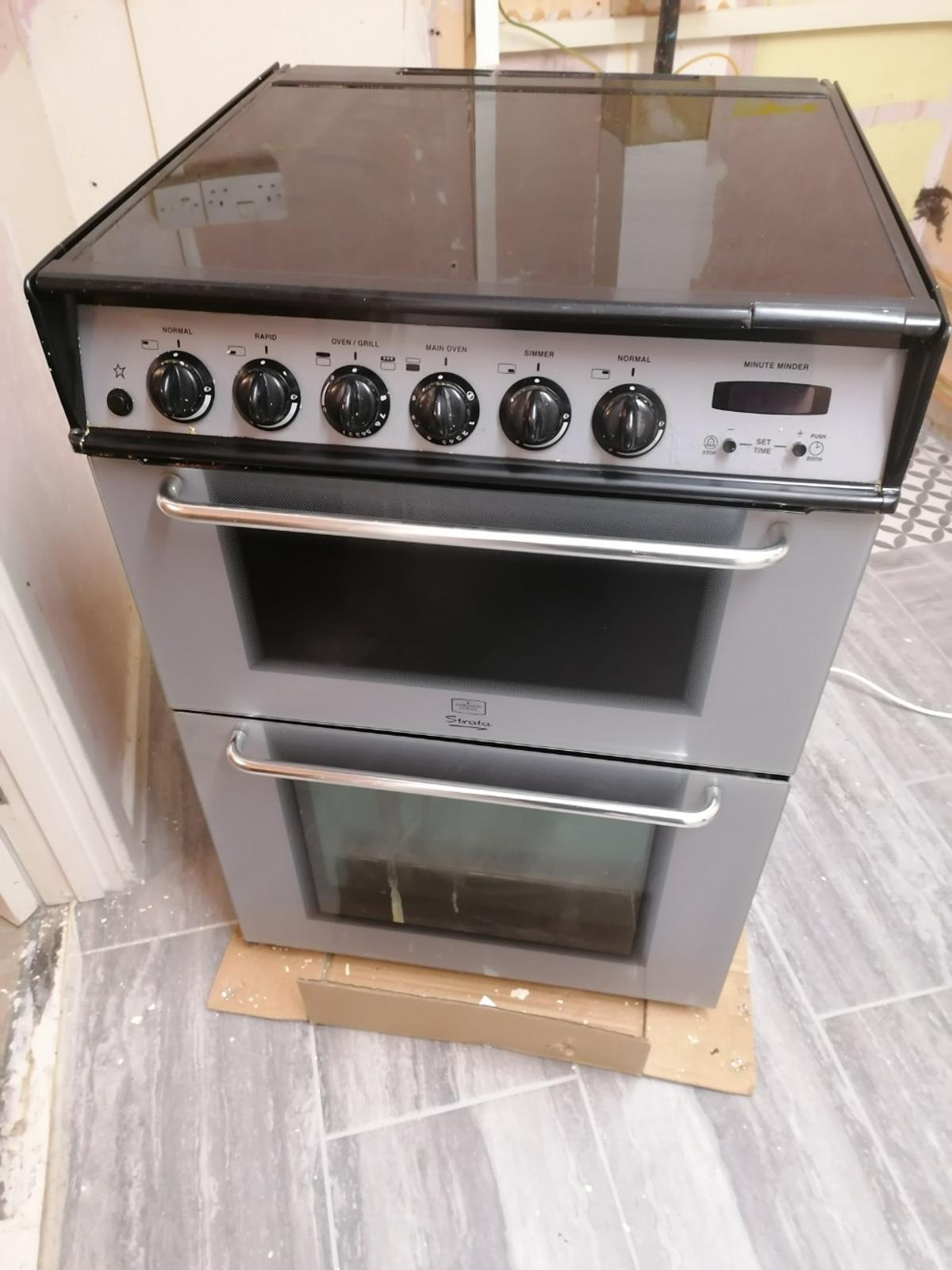 Freestanding Strata double gas oven, grill and hob made by Parkinson Cowan. 600mm wide and 650mm deep. Comes with gas hose attached. Integrated, hinged top. Has two shelves. Electric clock display and timer. Comes from a smoke free and pet free home.