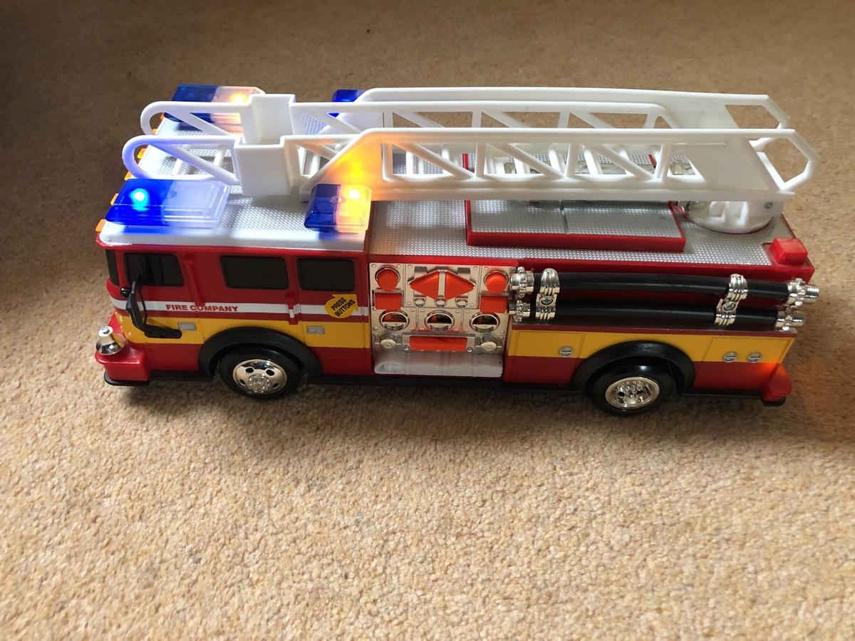 Battery operated flashing fire truck with extendable ladder.