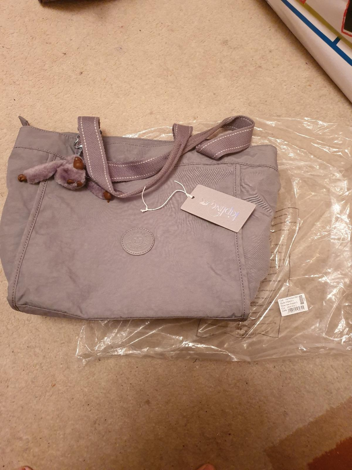 Kipling handbad new with Tags. in grey with monkey and long strap. lovely bag.