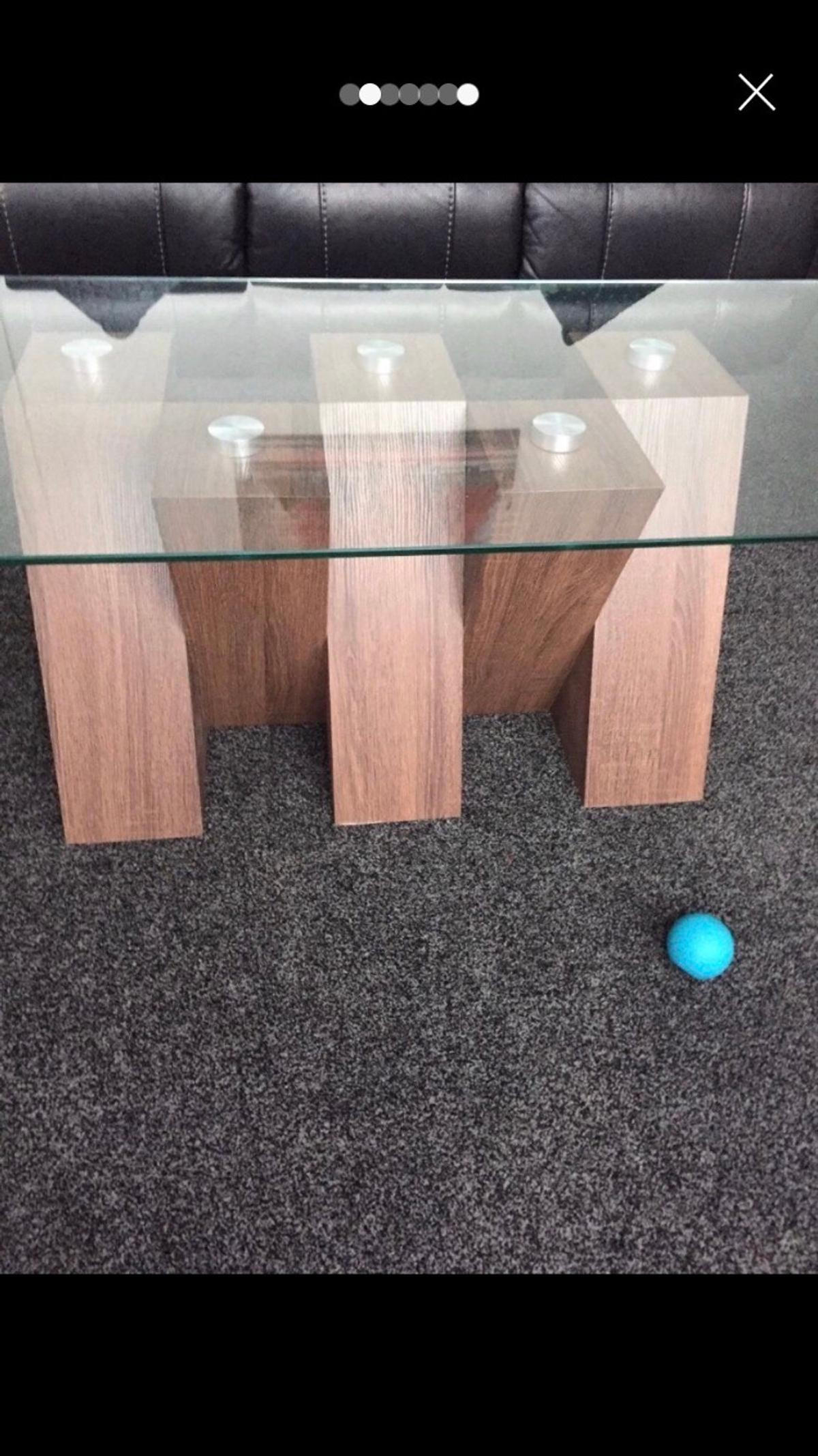 Really elegant coffee table with a heavy fixed glass top and teal wooden crossed legs, £380 new, brought as a present but not suitable for our room  Very heavy with strong glass and will need a car with seats down to collect  120cm long and 60 cm wide  Collection only smoke free home SE9 New eltham