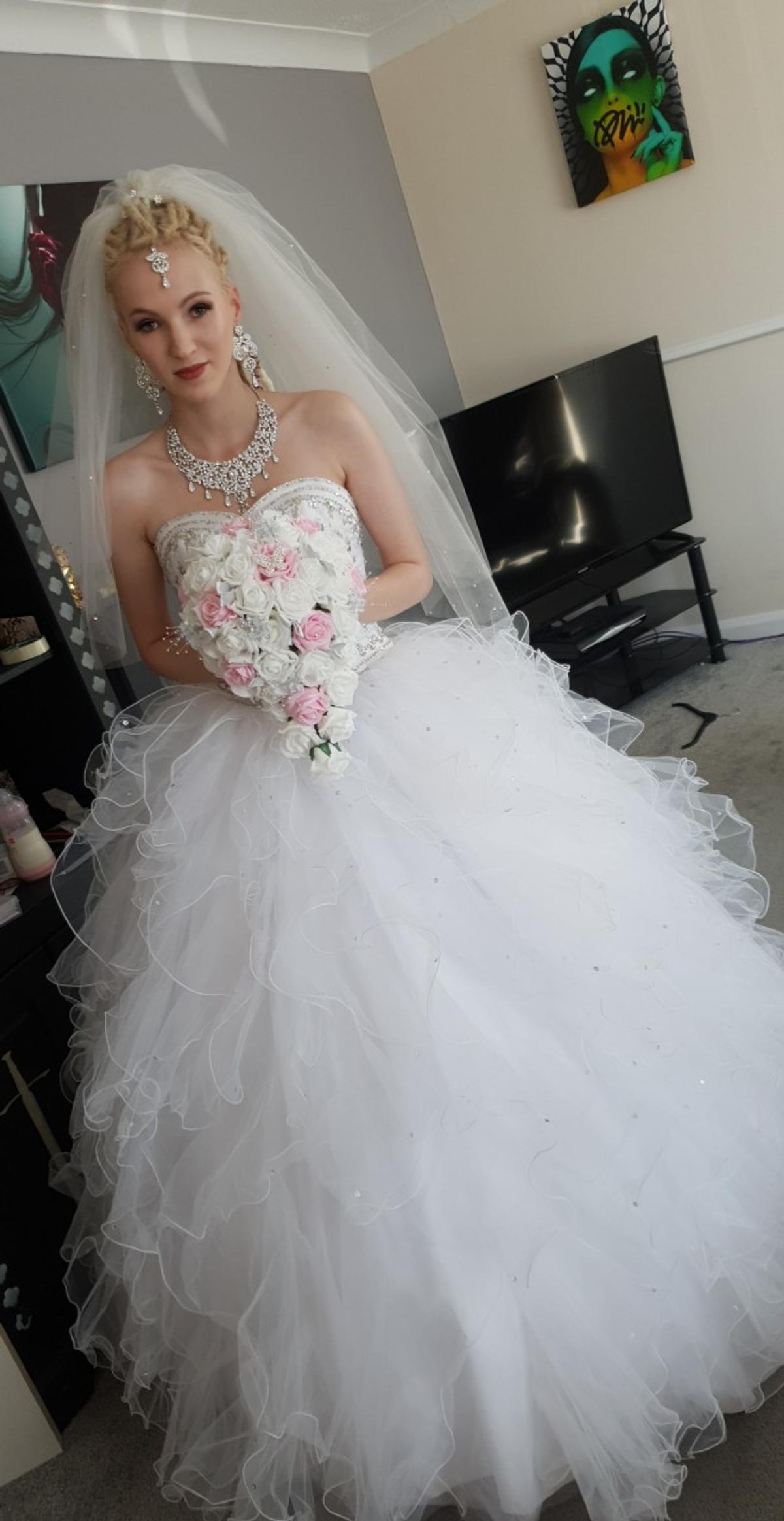 wedding dress and under skirt. size 6-8 but does have a corset back so may go bigger. jewels on the bodice. will need picking up.