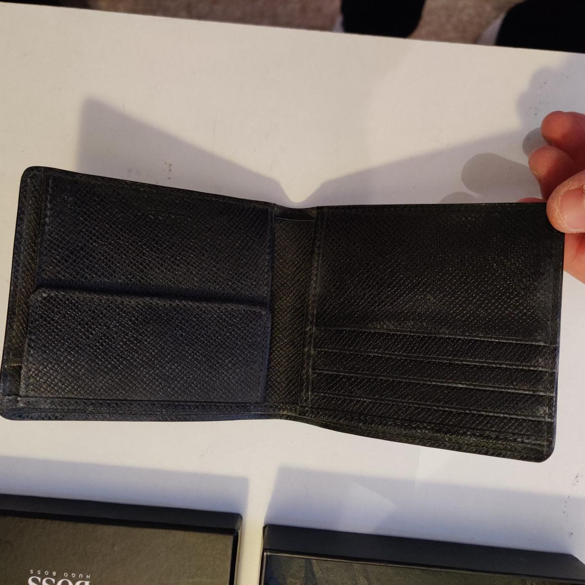 Striped leather wallet. Untouched and still in its box. Selling for 130 in store.