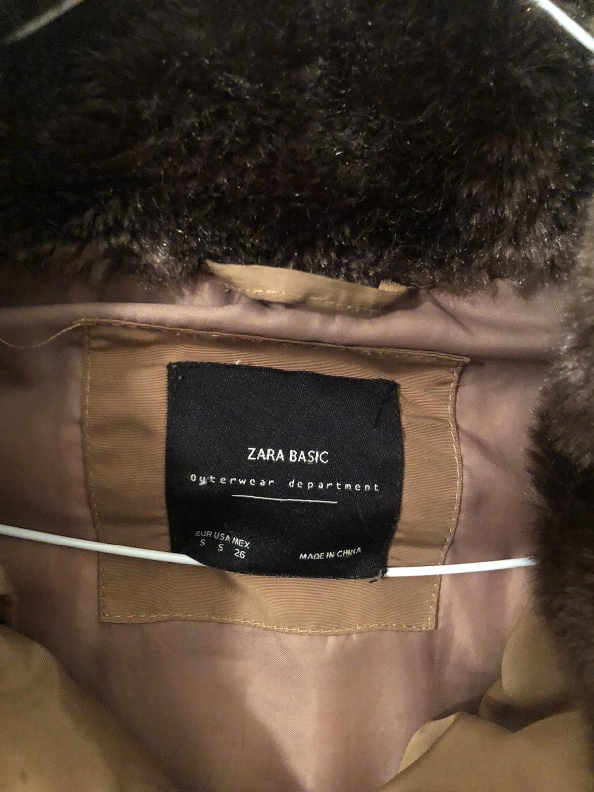 This is a beautiful jacket from Zara it has a stunning sandy/camel faux fur hood which is detachable (the fur is detachable and the hood all together is detachable). It has a gold zip to close and on pockets and has brown trim.