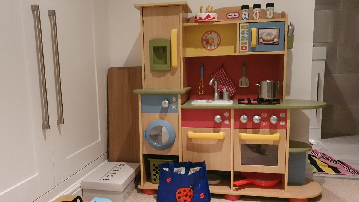 Children's kitchen has a double burner stove top, oven, and dishwasher all with clicking knobs  Pretend play refrigerator comes with ice dispenser  Pretend clock with hands that kids can move  Laundry center with washer/dryer and timer  Includes accessories including basket, play phone spatula, pots and pans, spice jars plus the mini tesco bag of play food.  images show slight crack in surface paint on washing machine and scuffing to the jacket potato  rrp new £170.