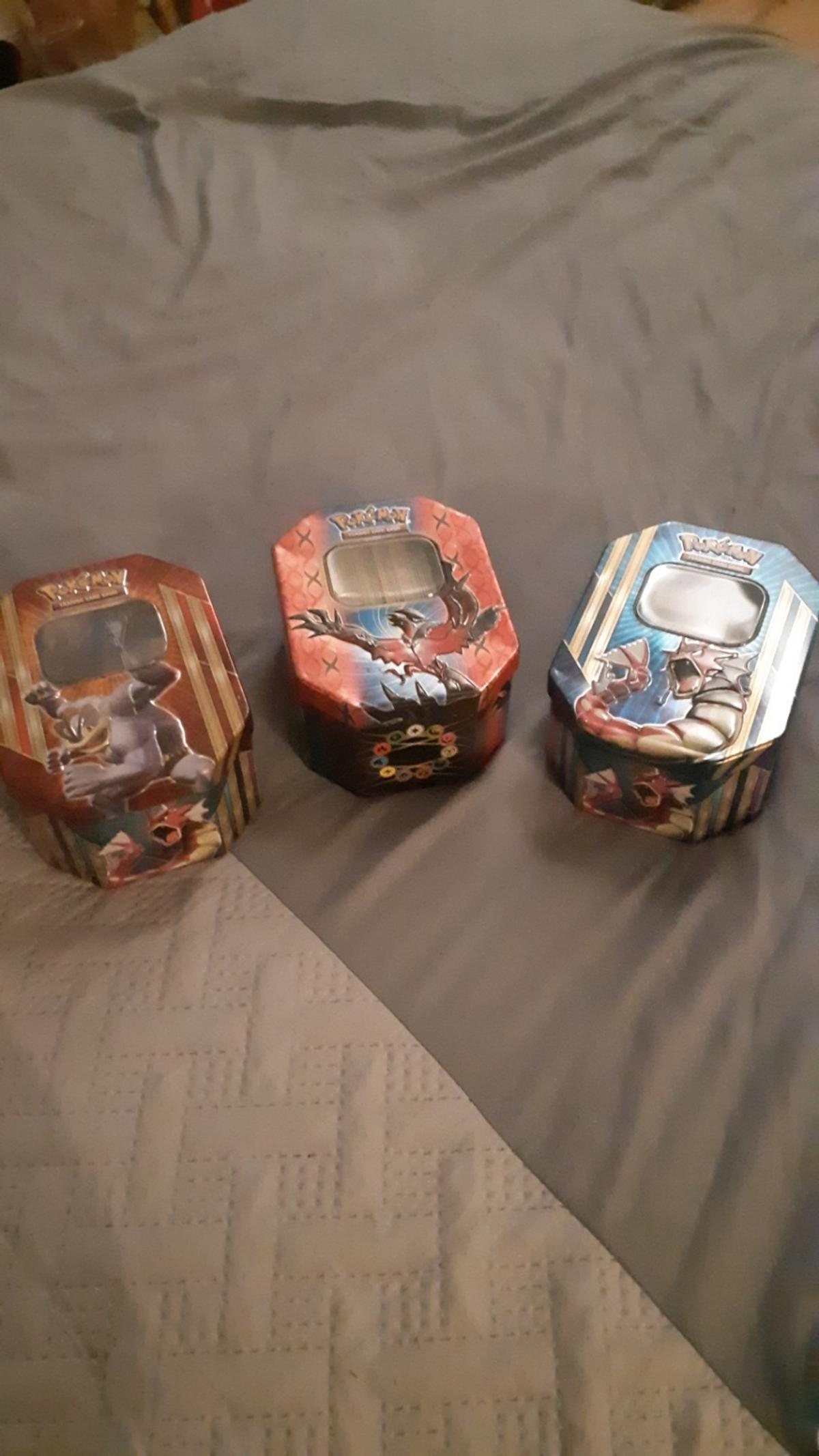 3 tins with lots of pokemon cards. pokemon game sheet with pokemon coins and rare cards