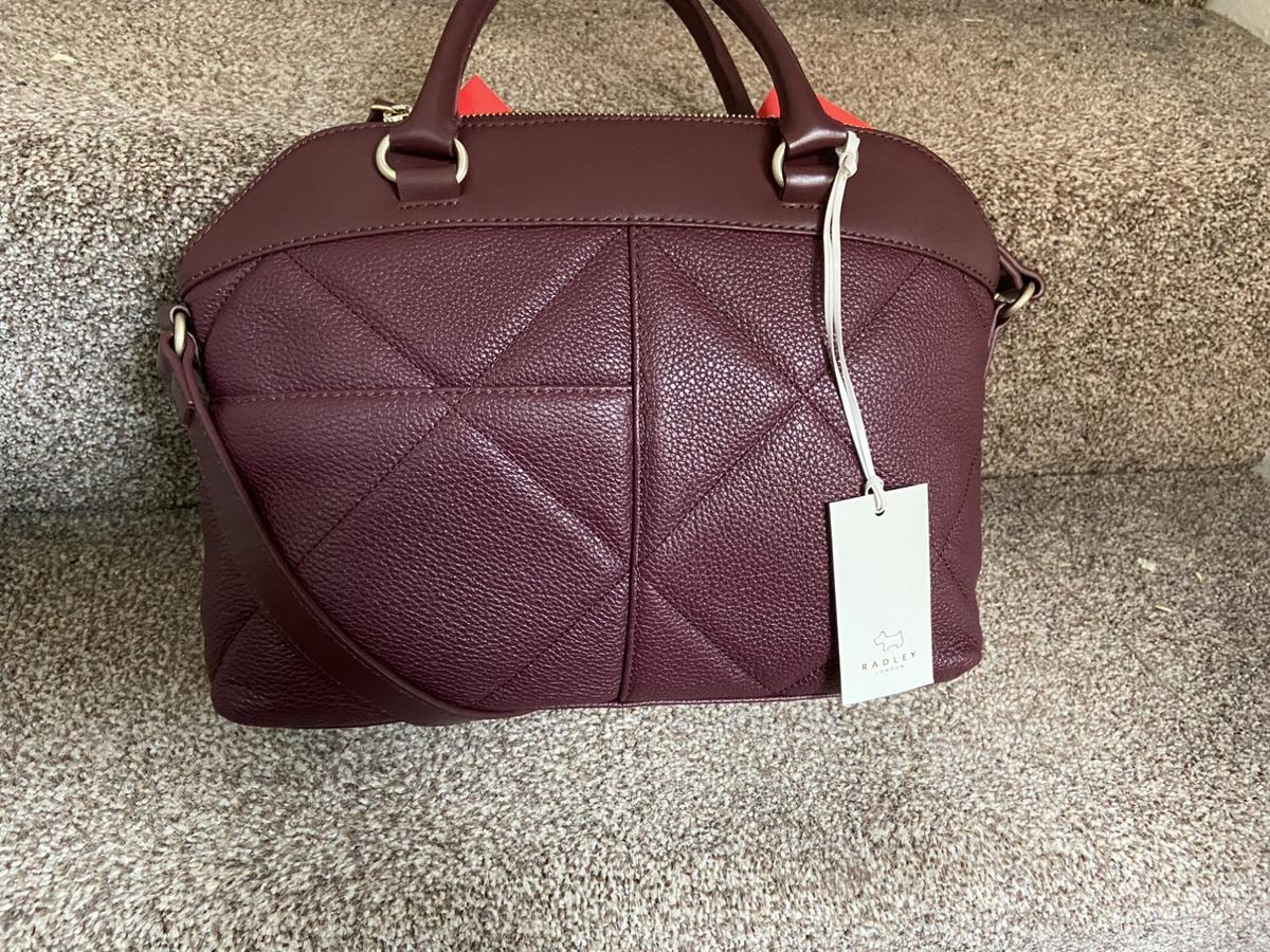 Leather. Burgundy in colour. With Tags. Comes with a shoulder strap to make it a more versatile bag & a Radley dust bag for protection. RRP £219