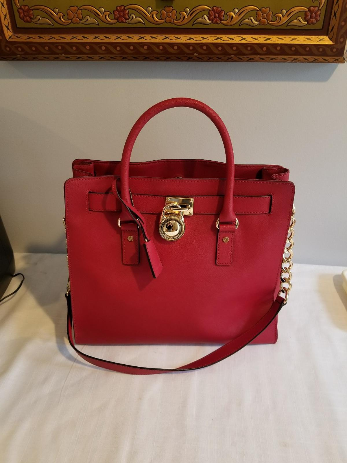 This sophisticated Michael Kors tote is crafted in solid saffiano leather with gold-tone hardware. A logo lock accents the front. The magnetic top line opens to a logo-lined, 5-pocket interior with spring-lock keychain. Rolled handles and shoulder strap.
