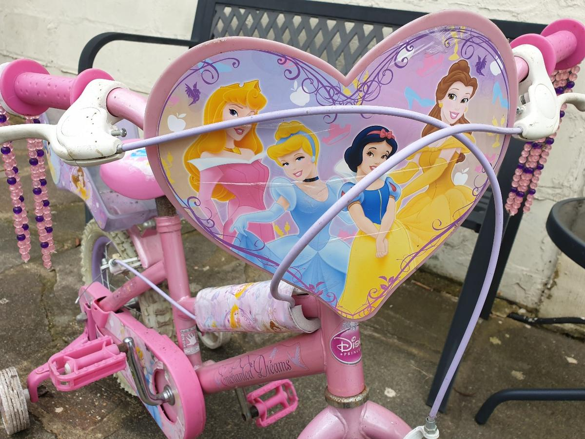 """Girls """"Enchanted Dreams"""" Disney Princess theme pink bike with rear carrier for those important items or best toys.14 inch wheels. Move forces sale. No offers under £15 please for this genuine bargain. Collection only from London Borough of Havering. Unable to deliver. Thanks for looking."""