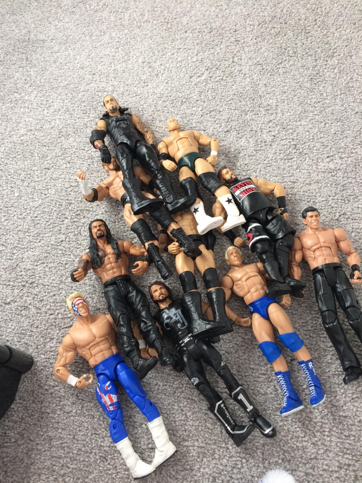 10 wwe action figures with accessories such as belts(titles) and a wrestling ring