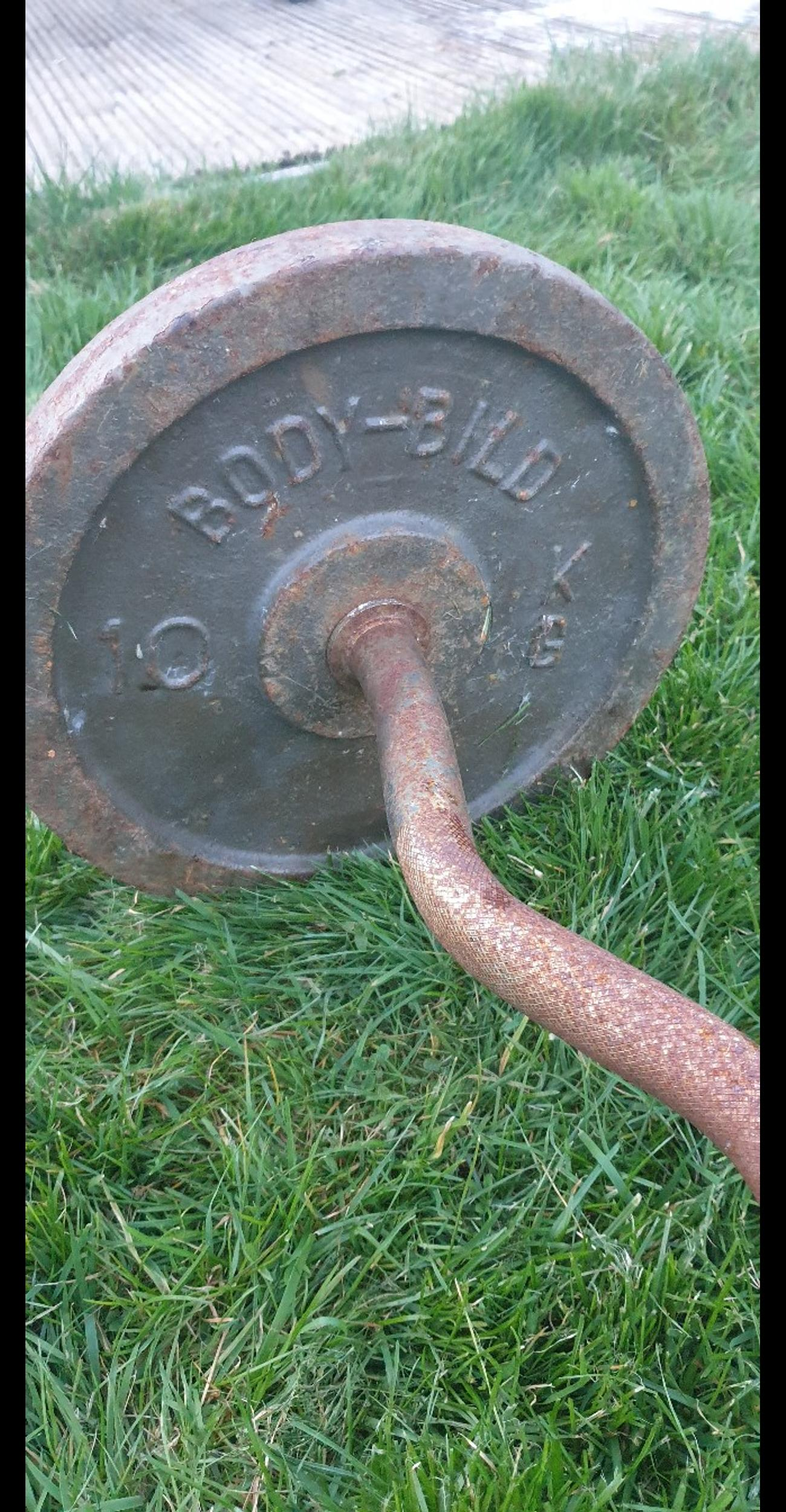 Curl Bar with 2x 10kg Weights. Has rust from where it's not been used and sat in shed for a long time.  Collection only