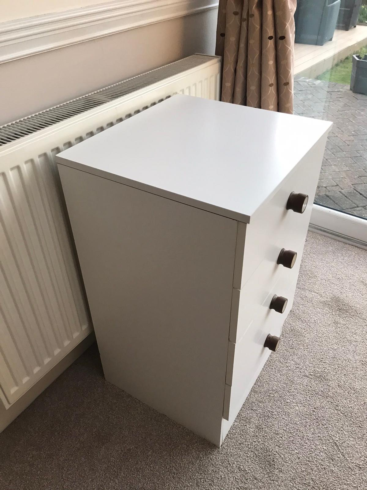 White chest of drawers with wood handles. A really solid piece of furniture.