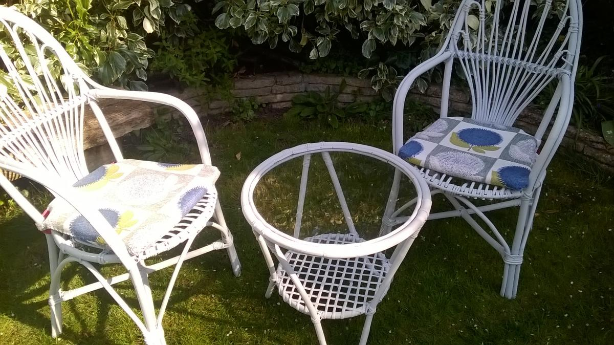 SET of 2 wicker conservatory chairs with cushions & a coffee table Painted chalk light grey (jar of paint included) Table 54 cm in diameter & 52 cm tall. Both chairs 100 cm tall & 52 cm wide each. Used & one chairs seat has 2 snapped reeds (pic 4) but still fine to seat on and plenty of use in them - also offered at a v reasonable price :) Used in our conservatory, balcony and out in the garden during the nice weather only so wood is NOT in any way rotten Local delivery available at a low price
