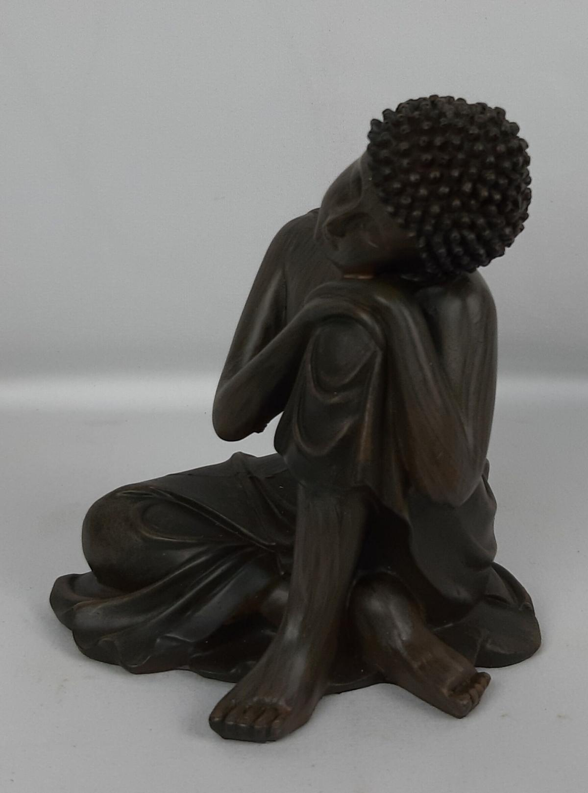 The story goes that Siddhartha Gautama left a life of luxury in pursuit of enlightenment. This statue depicts Buddha resting his head onto his knee.  Material: Resin  Dimensions: Height 12 cm, Width 11 cm  Weight: 280 g