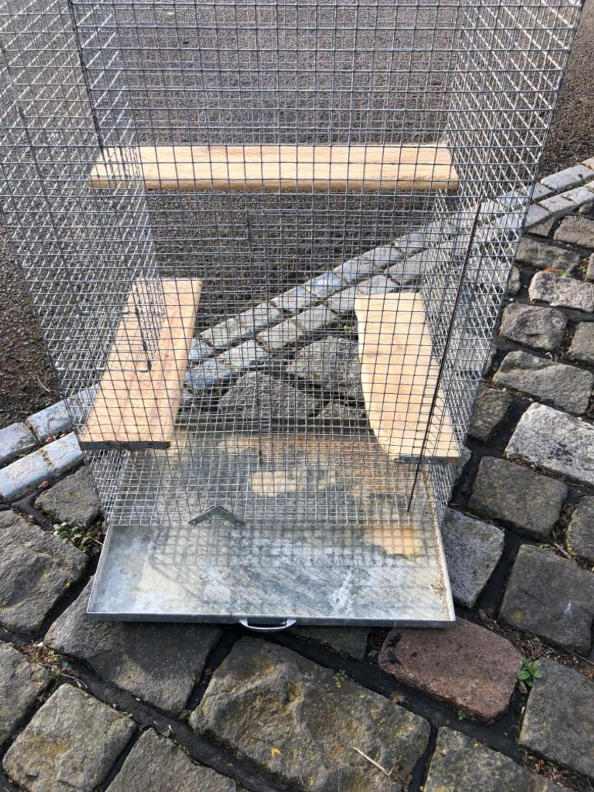 Animal cage with wooden perches and a pull out metal tray for cleaning. 3 available but each one has the perches in different places.