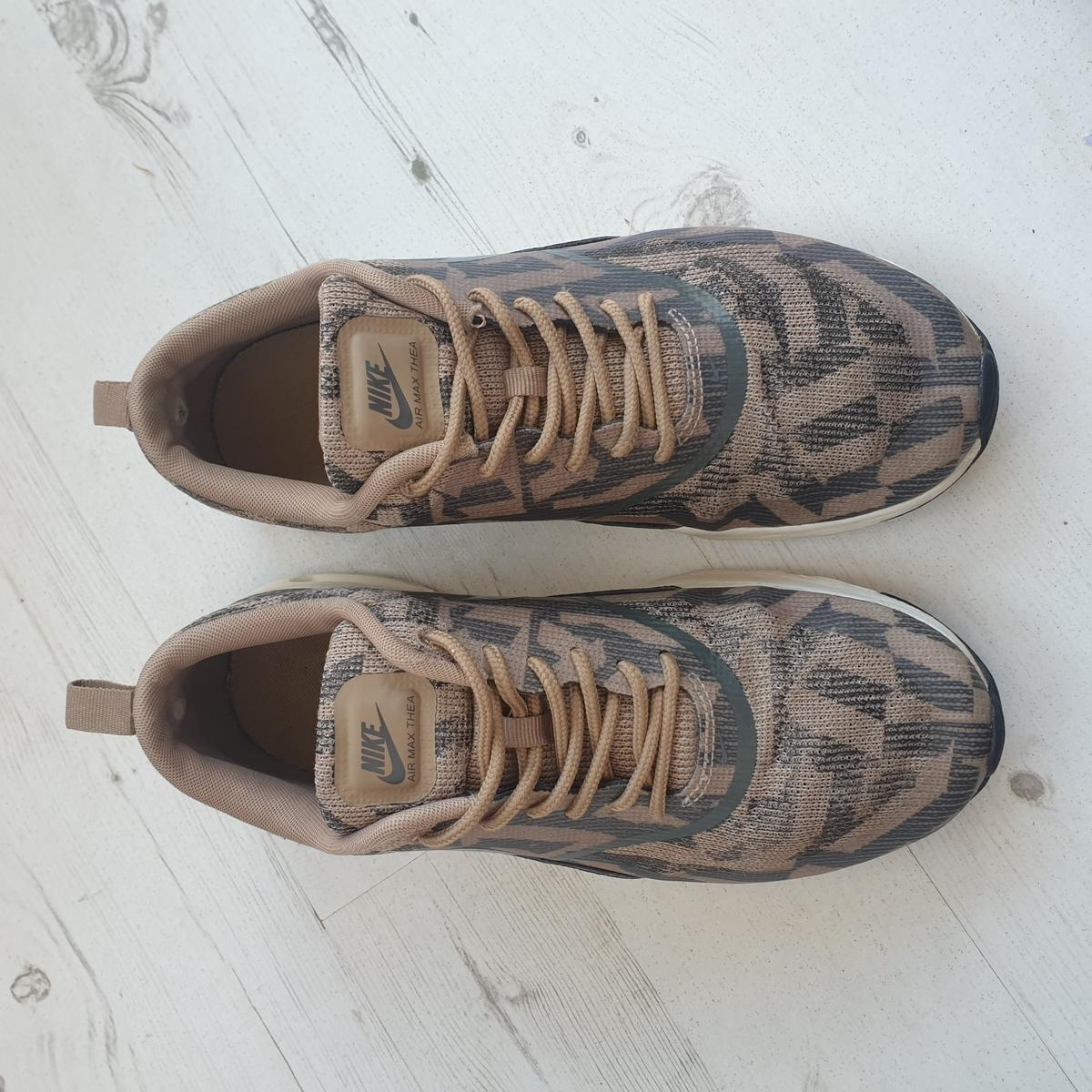 Khaki green print. Slight staining to inside sole, and slight wear on inside heel. otherwise, good condition.