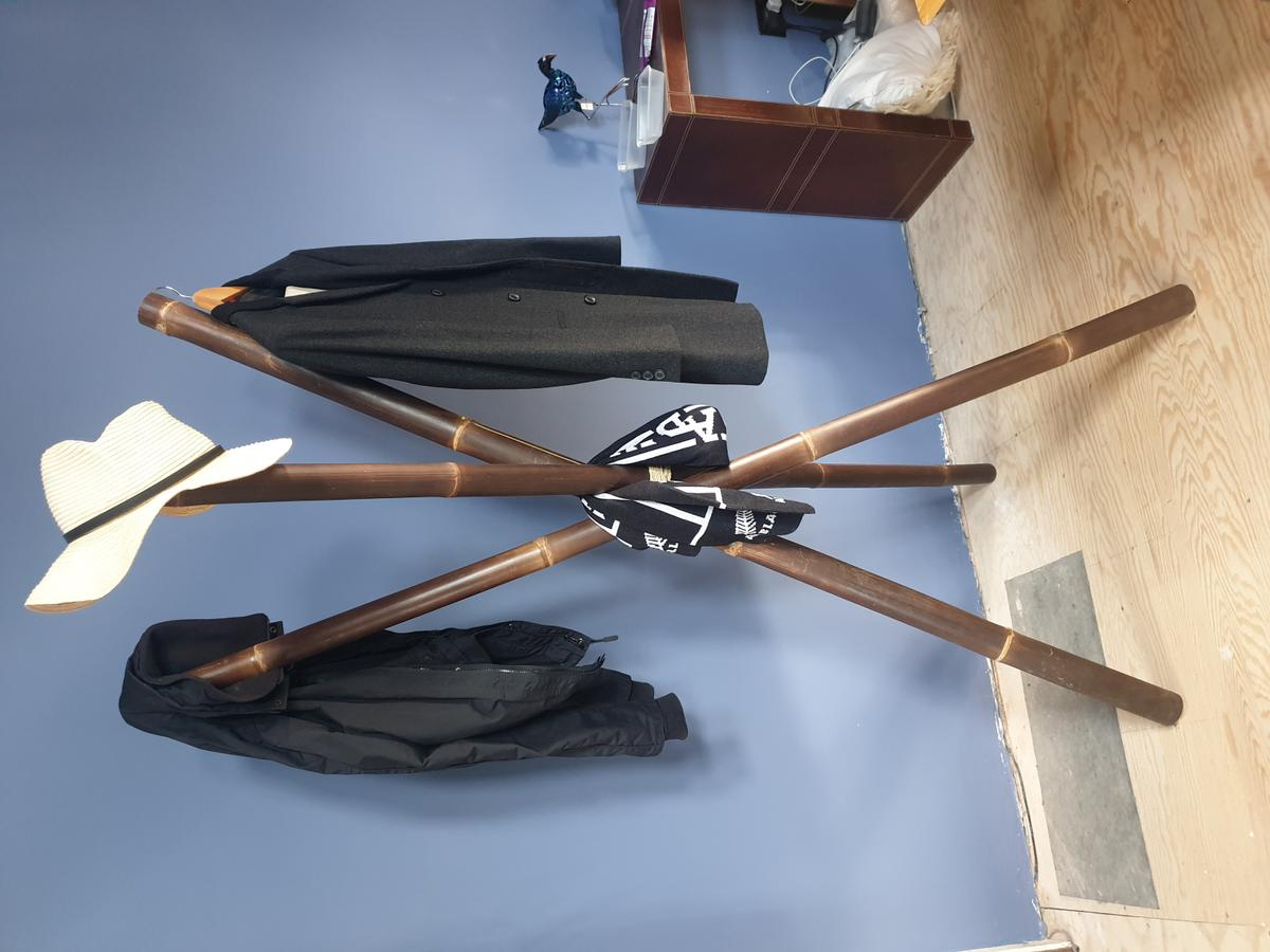 Brown bamboo coat hat stand.  Stands circa 6 feet tall and 2 feet diameter at bottom. Each leg is circa 2.5 inches wide. It collapses for transportation so that the 3 bamboo legs are bundled together.