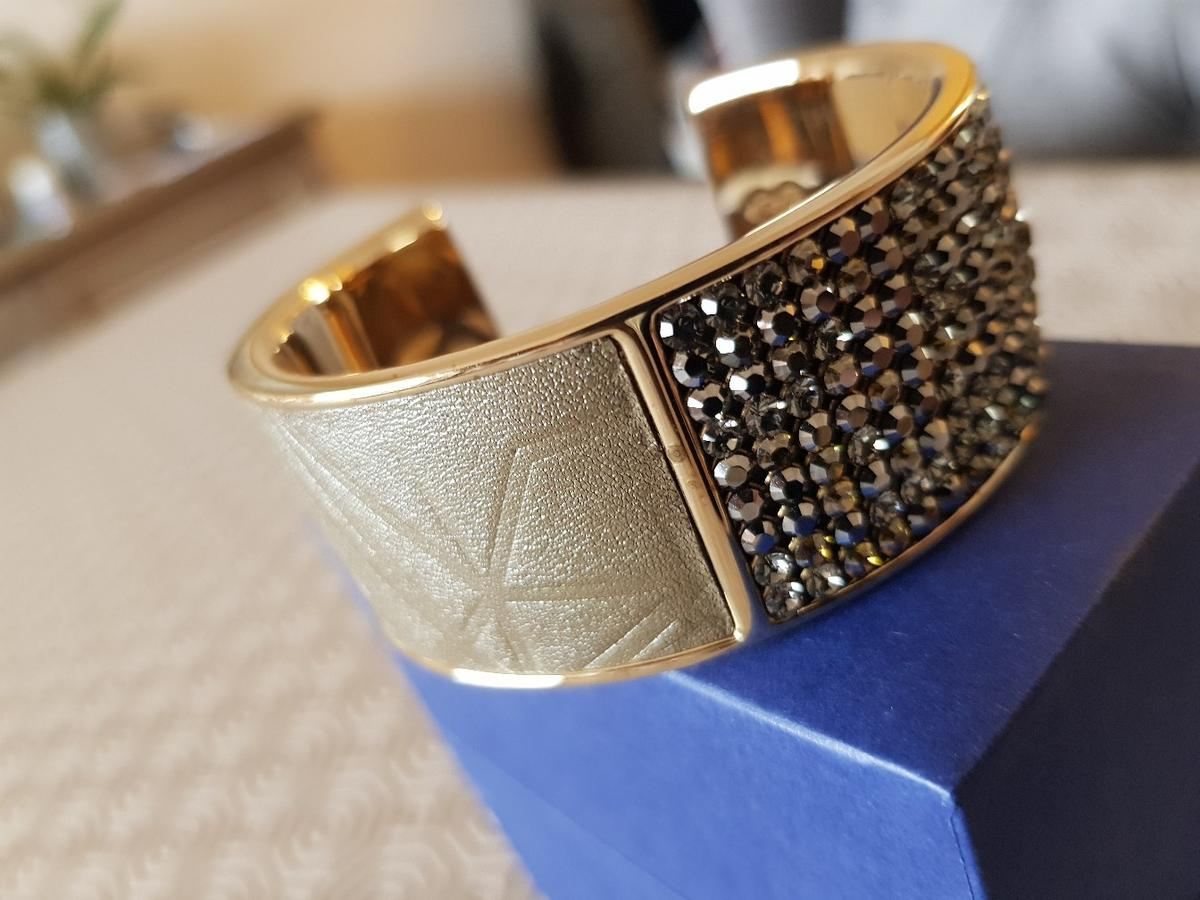 gold wide bangle with a soft khaki green leather on half and khaki matching stones on the other.