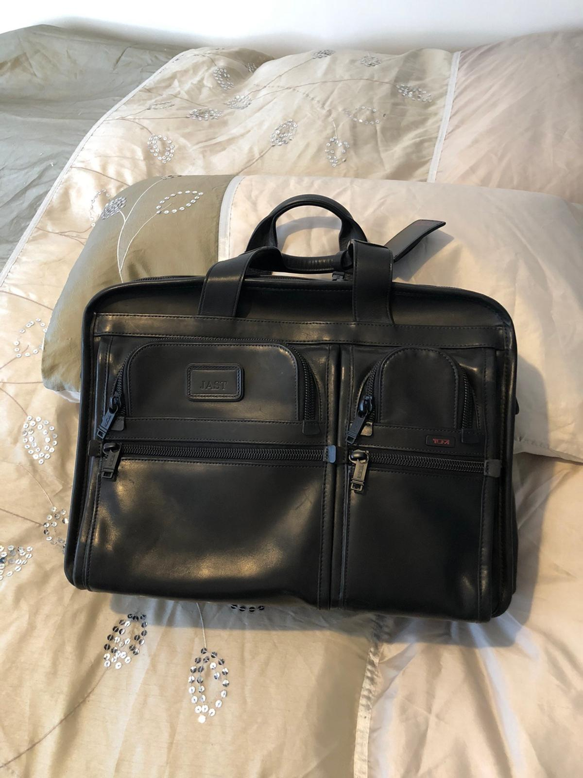 Tumi black leather expandable organizer laptop briefcase. This bag is perfect for both commuting to work or as an over night bag. You will be getting a great bag that looks brand new while paying a fraction of the price of a new one. Comes with a shoulder strap.