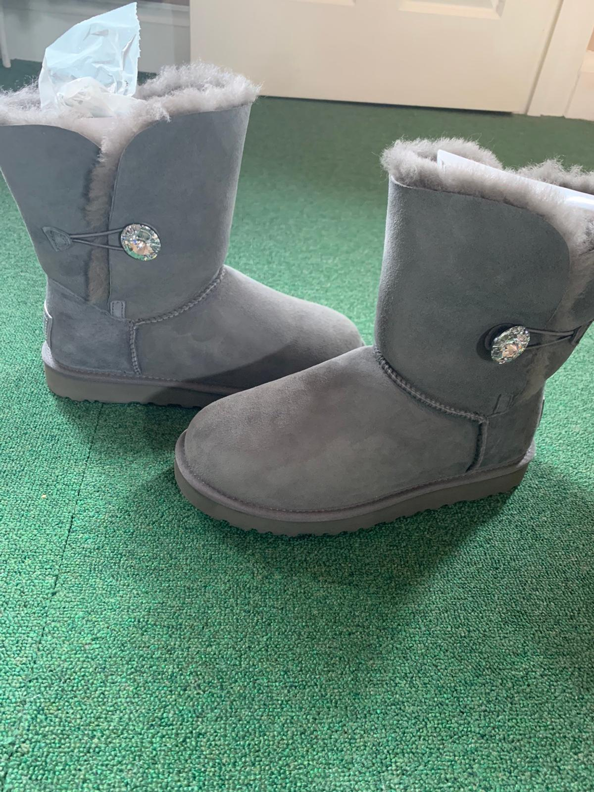 Authentic Grey suede ladies UGG boots. Bailey Bling with Swarovski Crystal label and button. With the hologram label for authenticity. Size as stated on the box: USA 8 UK 6.5 EU 39 Japan 250 Never been worn.