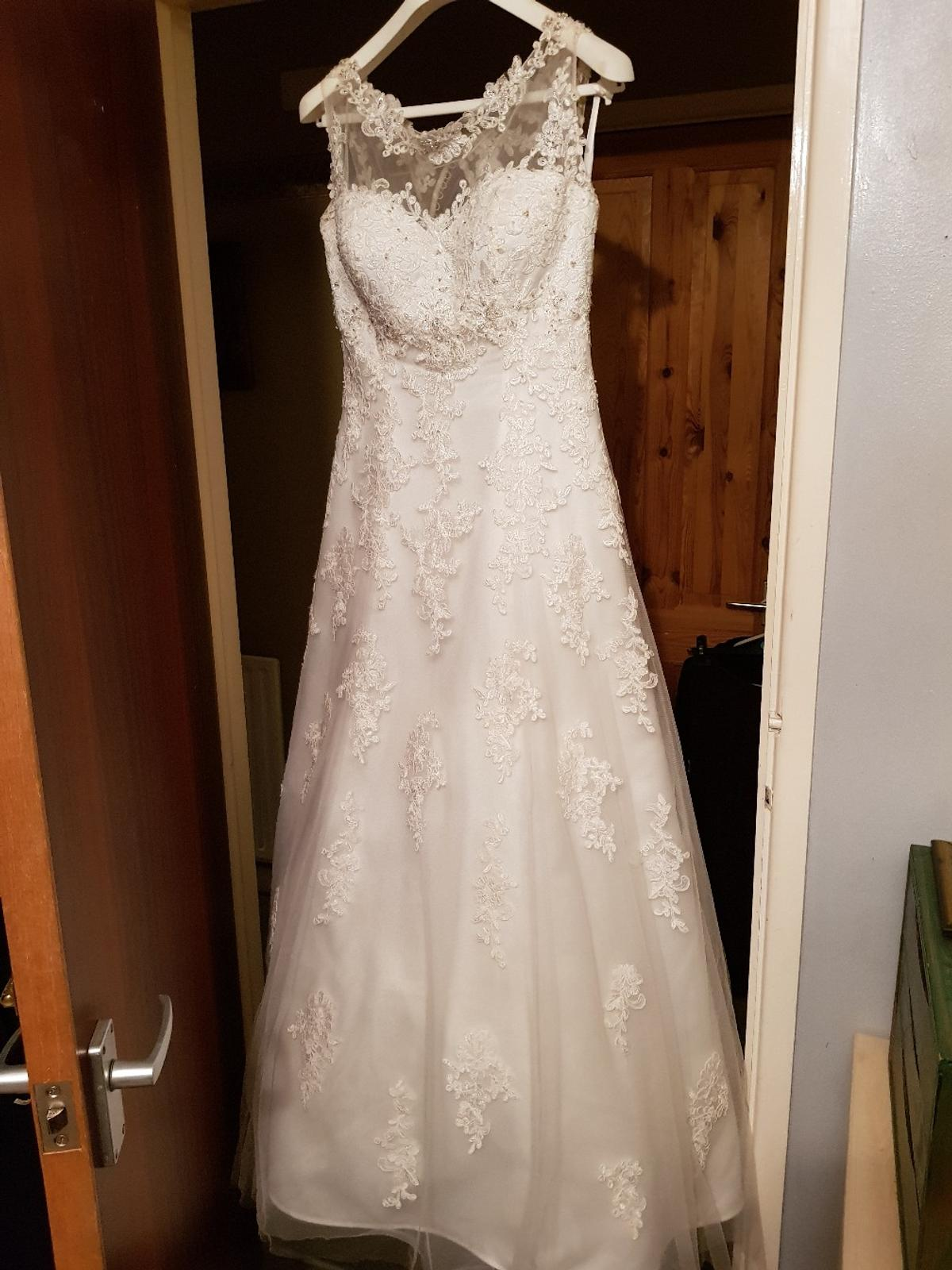 Absolutely stunning Lillian West wedding dress size 12 with illusion neck line. Will need a dry clean but only worn on the day. Ivory and silver. Bought it at £1,800. In perfect conditions, just a few slits on the mesh as in the pictures. The train picks up and hooks on the back as in picture to make the entire back exact floor length as the dress itself.