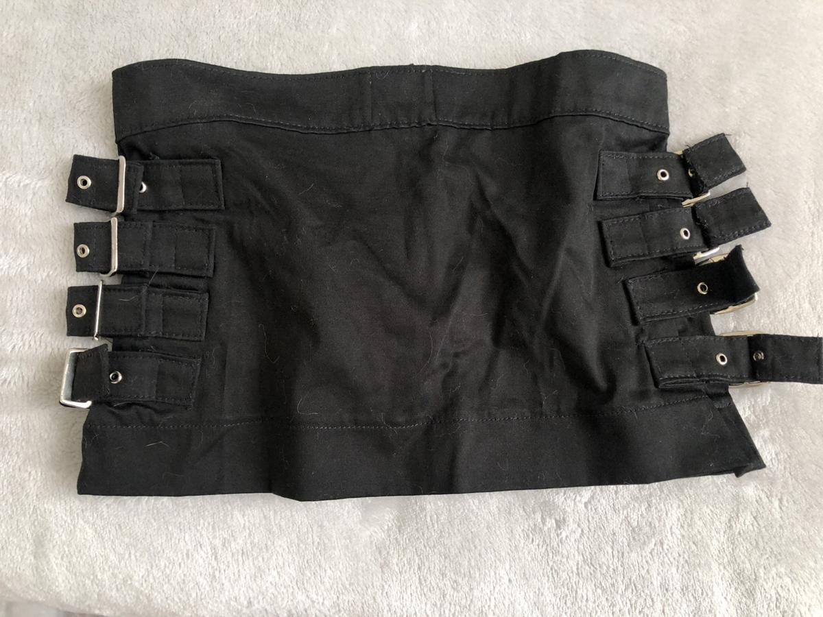 Very short miniskirt with strap/buckle details at the sides.