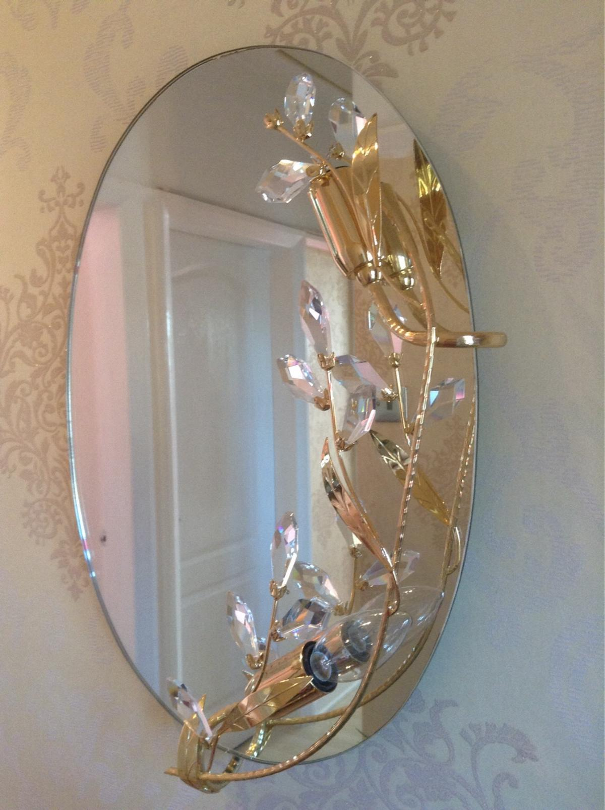 Beutifull ovel mirror with Cristles also it takes 2 bulbs it measures. Hight 181/2 ins with is 13ins at the centre also Gold Edging to one side