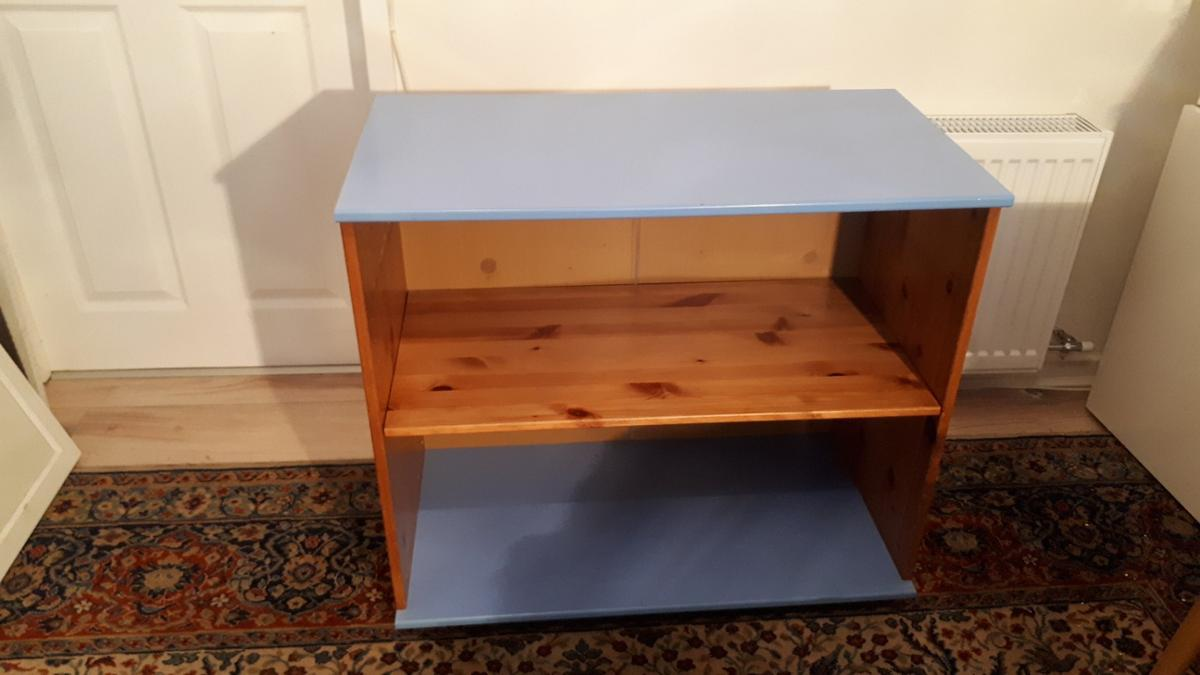 With pine sides and shelf, blue lacquered top and bottom, this useful unit could be used in a number of ways. *16 positions to adjust the shelf. *Has 4 silver wooded feet. *Hardboard back. Originally may have had a top shelf ( now removed) which has left a couple of marks on the inner sides, but these are not detrimental to the unit or it's look. Some tiny bubbles and little scratches to paint on blue lacquered top. . again hardly noticeable. Height 72cm Width/Length 80cm Depth 43cm
