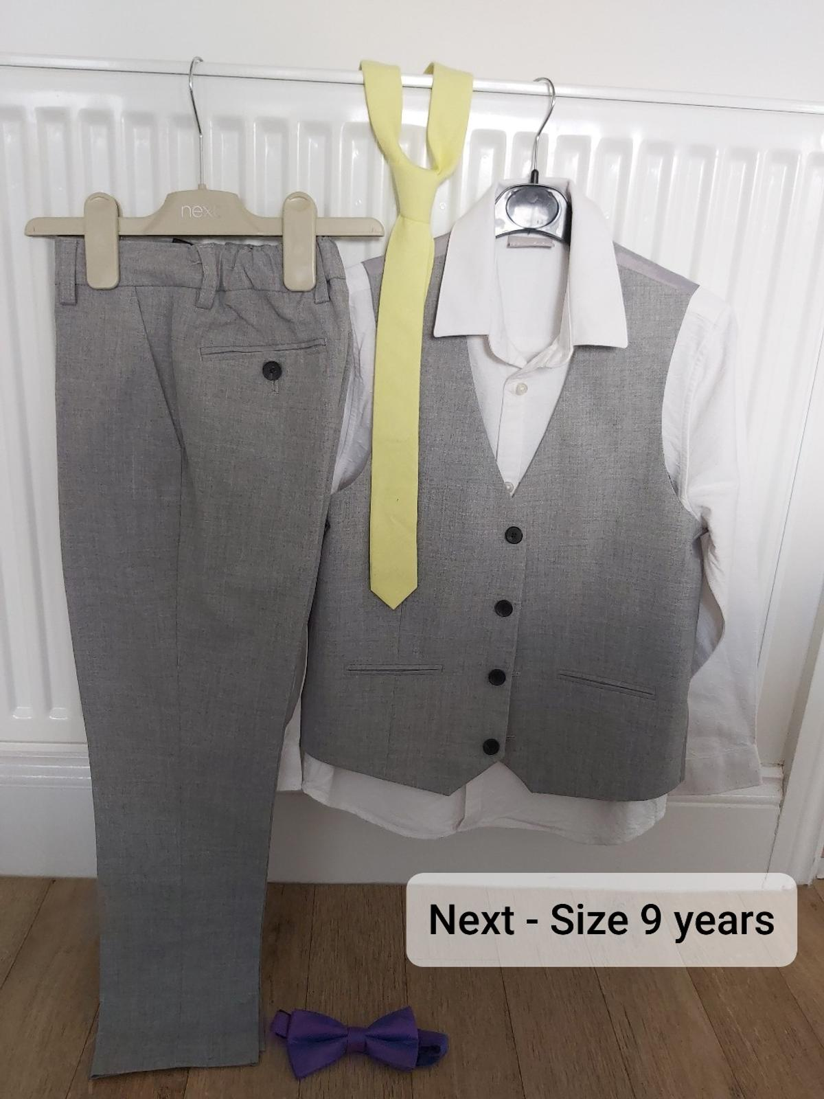 Next three piece suit comprising of grey trousers & waistcoat & a white long sleeved shirt. Also includes a yellow tie & purple bow tie.  Size 9 years.  In excellent condition, only been worn once.