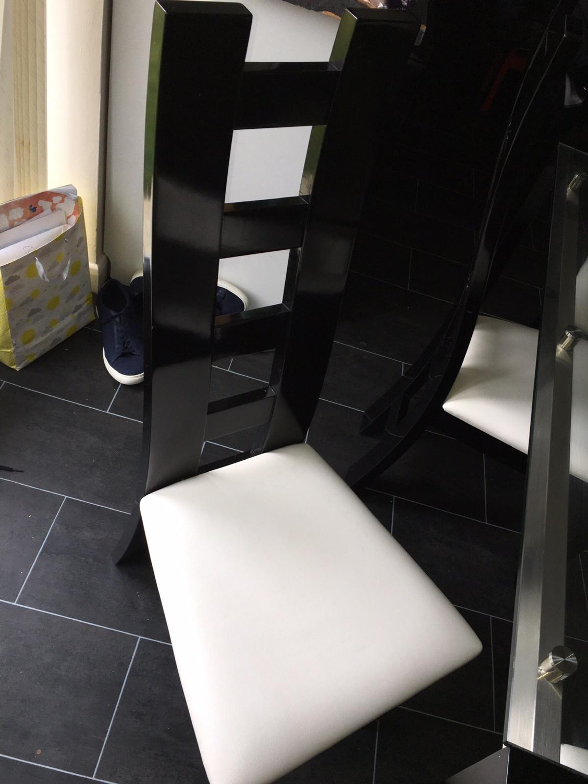 Glass and black gloss dining table with 6 chairs. Good condition some small marks on the table and a small mark on one chair but not noticeable and doesn't effect use. Must go this weekend. Collection only!